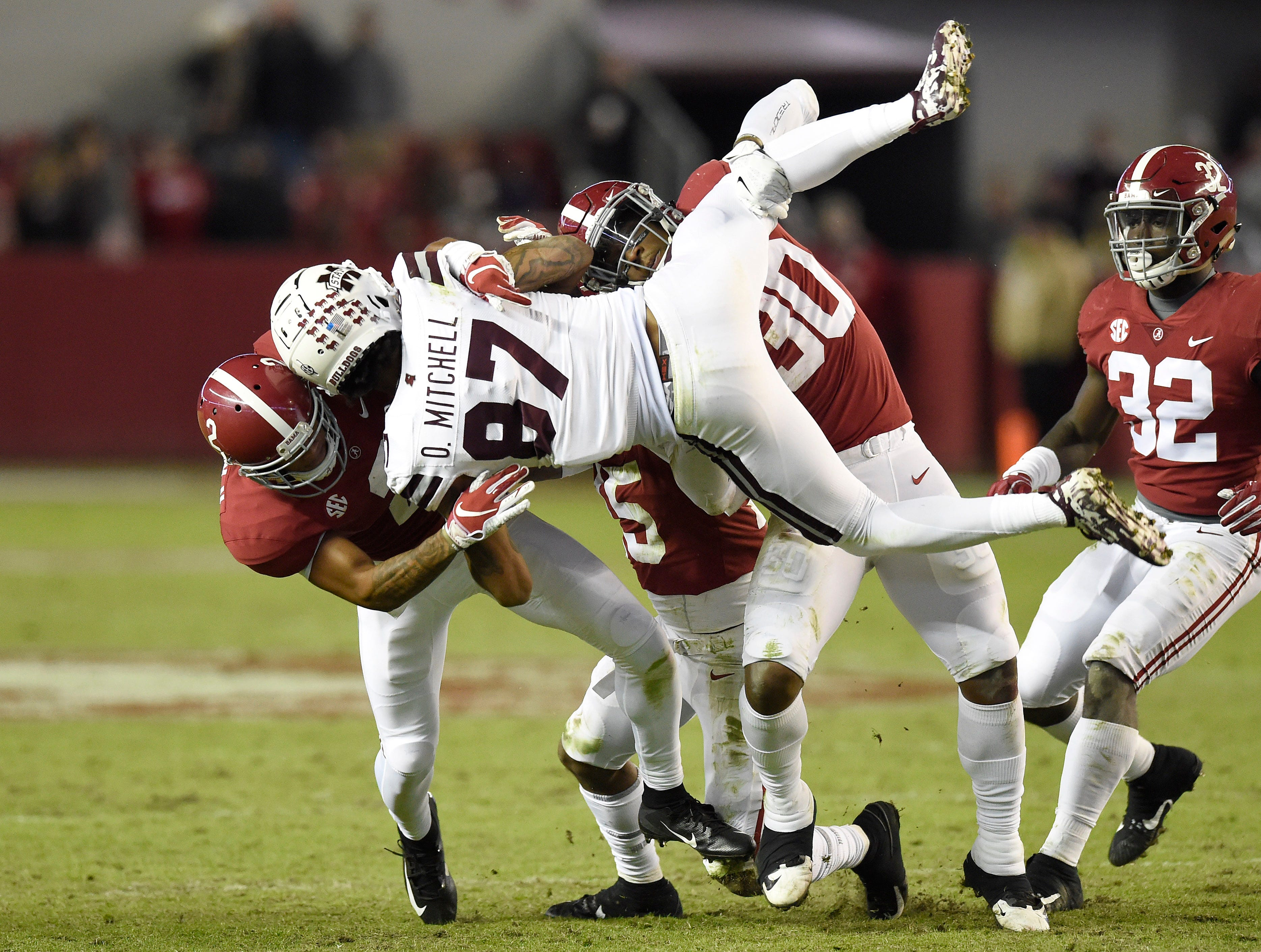 Mississippi State Bulldogs wide receiver Osirus Mitchell (87) gets tackled by Alabama Crimson Tide defensive back Patrick Surtain II (2) and linebacker Mack Wilson (30) during the fourth quarter at Bryant-Denny Stadium.