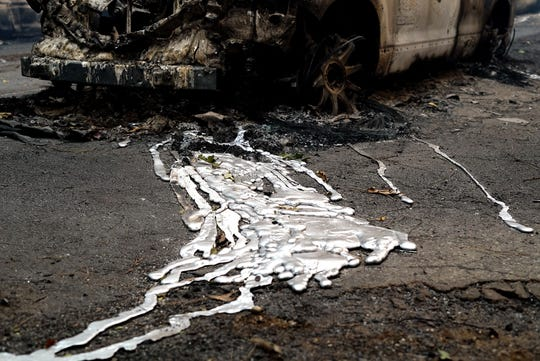 Nov 10, 2018; Paradise, CA, USA; Melted aluminum that ran out of an abandoned car hardened in the roadway after the Camp Fire passed through Paradise, California. Mandatory Credit:  Trevor Hughes-USA TODAY ORIG FILE ID:  20181110_ajw_usa_268.jpg
