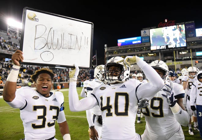 "Georgia Tech Yellow Jackets defensive backs Jaytlin Askew (33) and Kaleb Oliver (40) hold up a sign that reads ""Bowlin""  after defeating the Miami Hurricanes at Bobby Dodd Stadium for their sixth win."