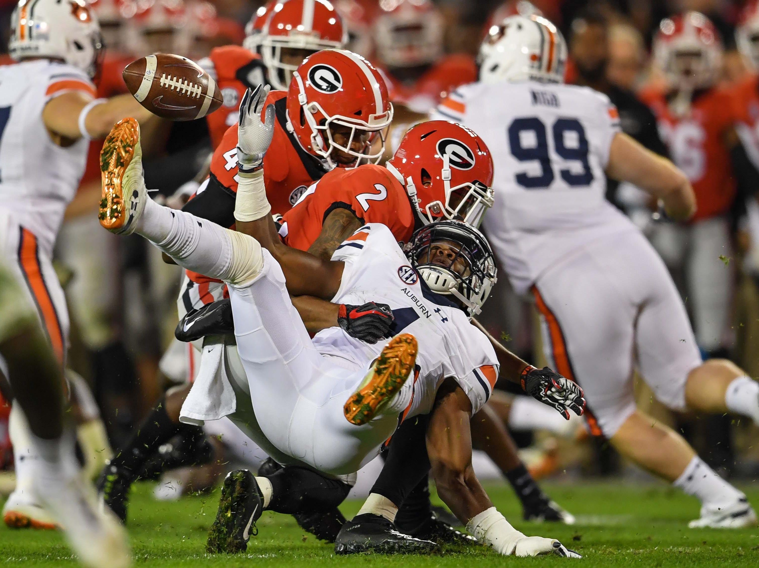 Week 11: Auburn Tigers kick returner Noah Igbinoghene (4) fumbles after being hit by Georgia Bulldogs linebacker Robert Beal Jr. (not shown) during the first half at Sanford Stadium.