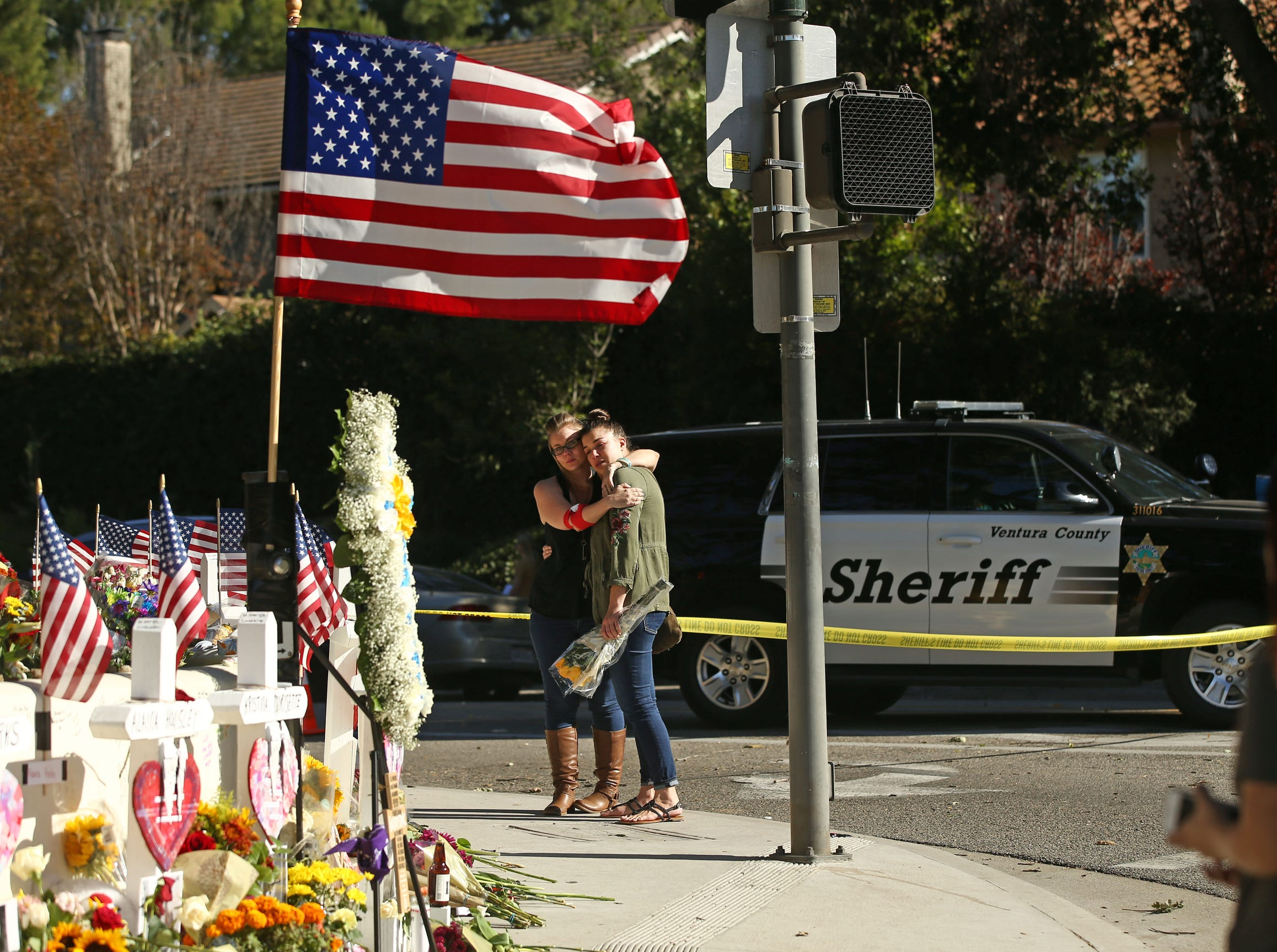 Peole mourn as the mass shooting victims' memorial grows Sunday, Nov. 11, 2018, in Thousand Oaks, Calif., as the FBI and Ventura County Sheriff's office continue their investigation at the Borderline Bar and Grill.