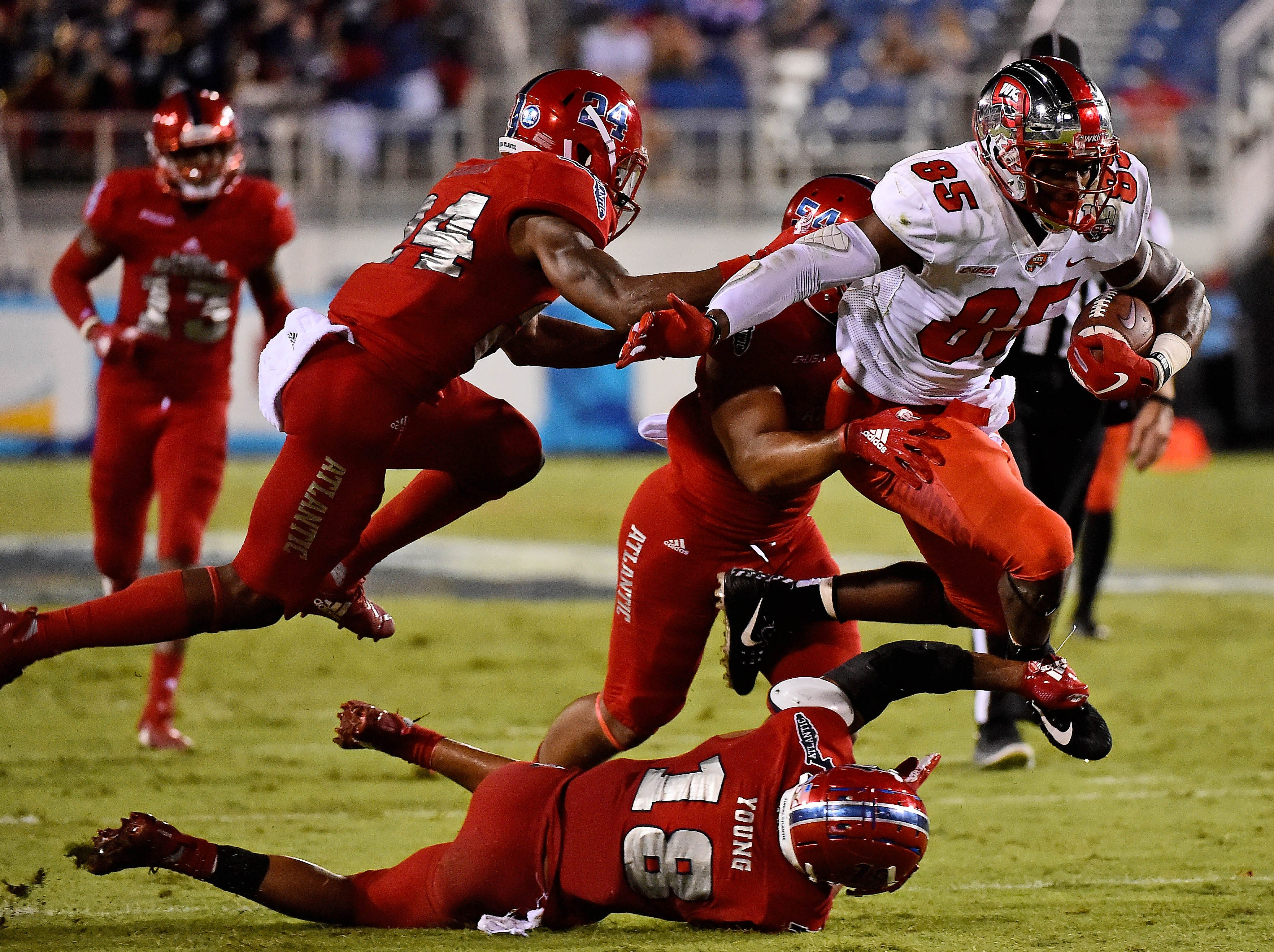 Western Kentucky Hilltoppers tight end Mik'Quan Deane (85) leaps over Florida Atlantic Owls safety Jalen Young (18) during the second half at FAU Football Stadium.