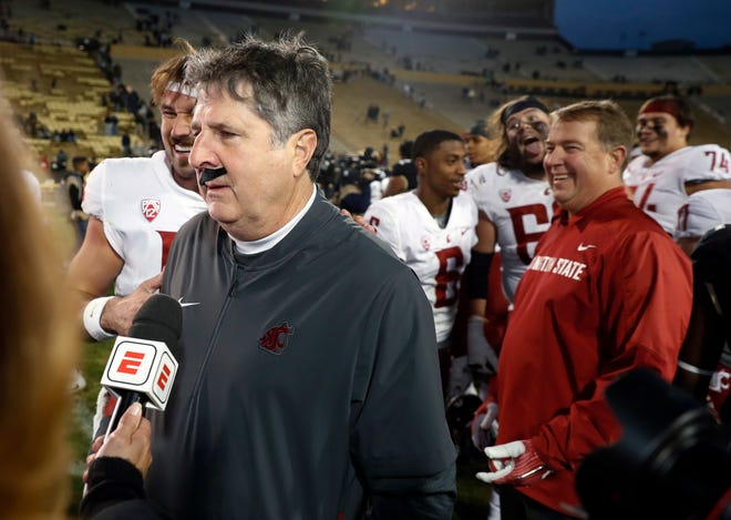 Washington State head coach Mike Leach wears a fake mustache placed on him by starting quarterback Gardner Minshew during a TV interview.