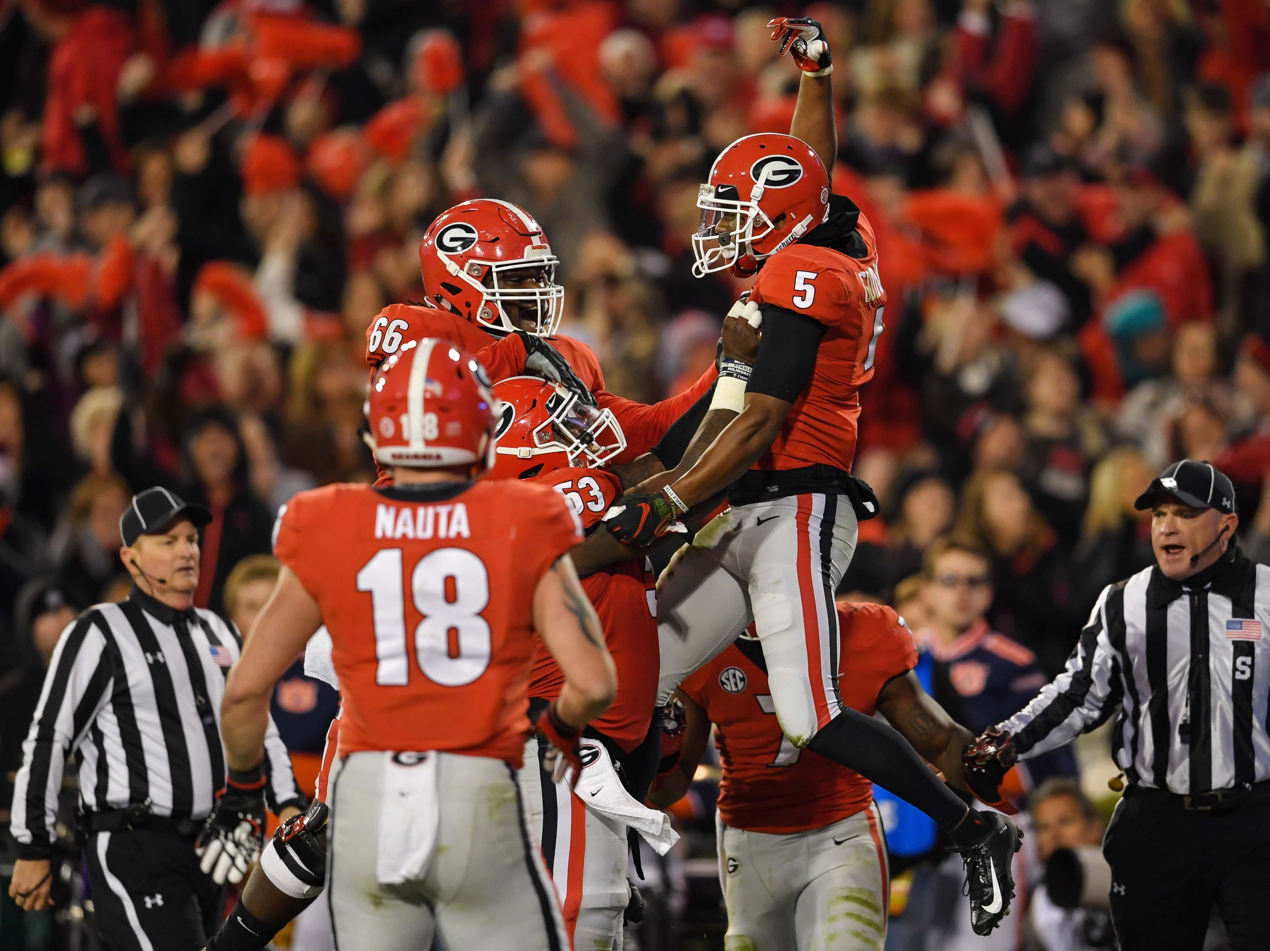 Georgia Bulldogs wide receiver Terry Godwin (5) reacts with teammates after scoring a touchdown against the Auburn Tigers during the first half at Sanford Stadium.