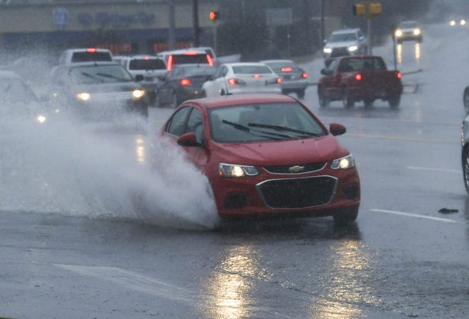 Vehicles drive slower through steady rain and partly flooded lanes on Clemson Boulevard in Anderson on Monday.