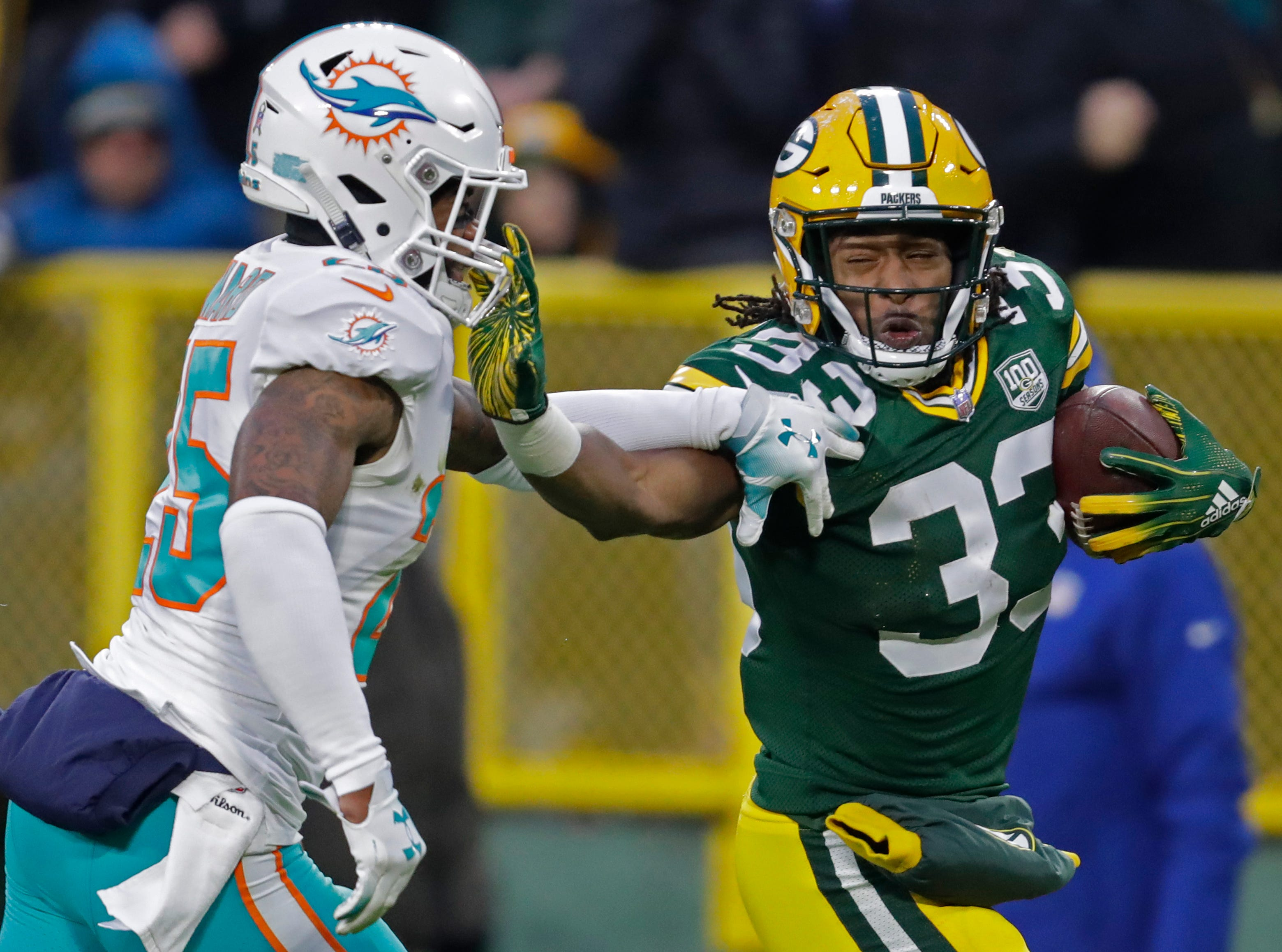Green Bay Packers running back Aaron Jones (33) stiff arms Miami Dolphins cornerback Xavien Howard (25) on a 67-yard run in the first quarter Sunday, November 11, 2018, Lambeau Field in Green Bay, Wis. 