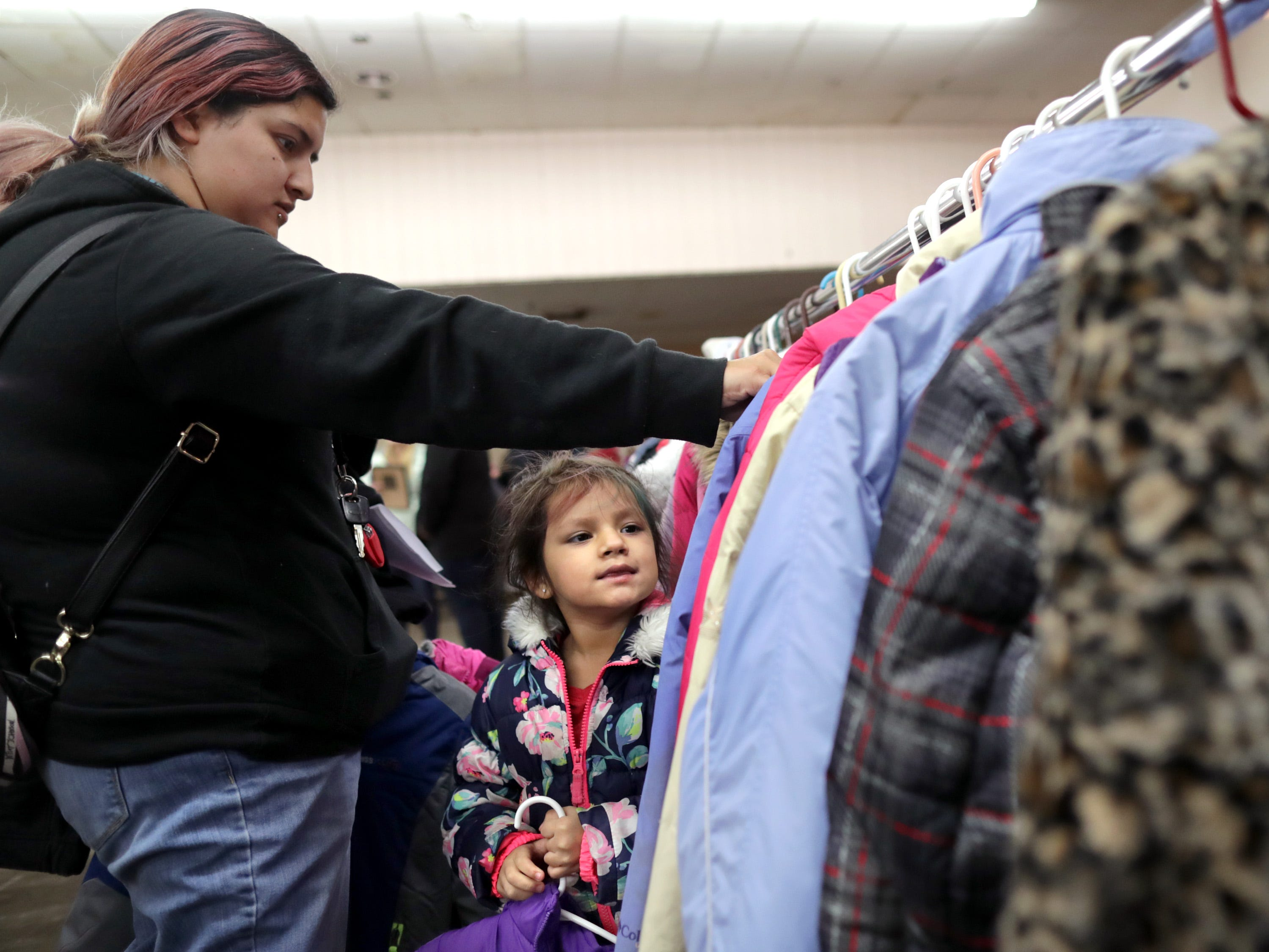 Amy Reyes and 3 year old Magnolia Perez look through a rack of winter coats during the annual Salvation Army Coats for Kids on Wednesday, November 7, 2018, in Kimberly, Wis. the distribution center ast Fox Valley Chrisian Fellowship Church in Kimberly will be open on Thursday November, 8 Friday November, 9 from 8 am until noon.