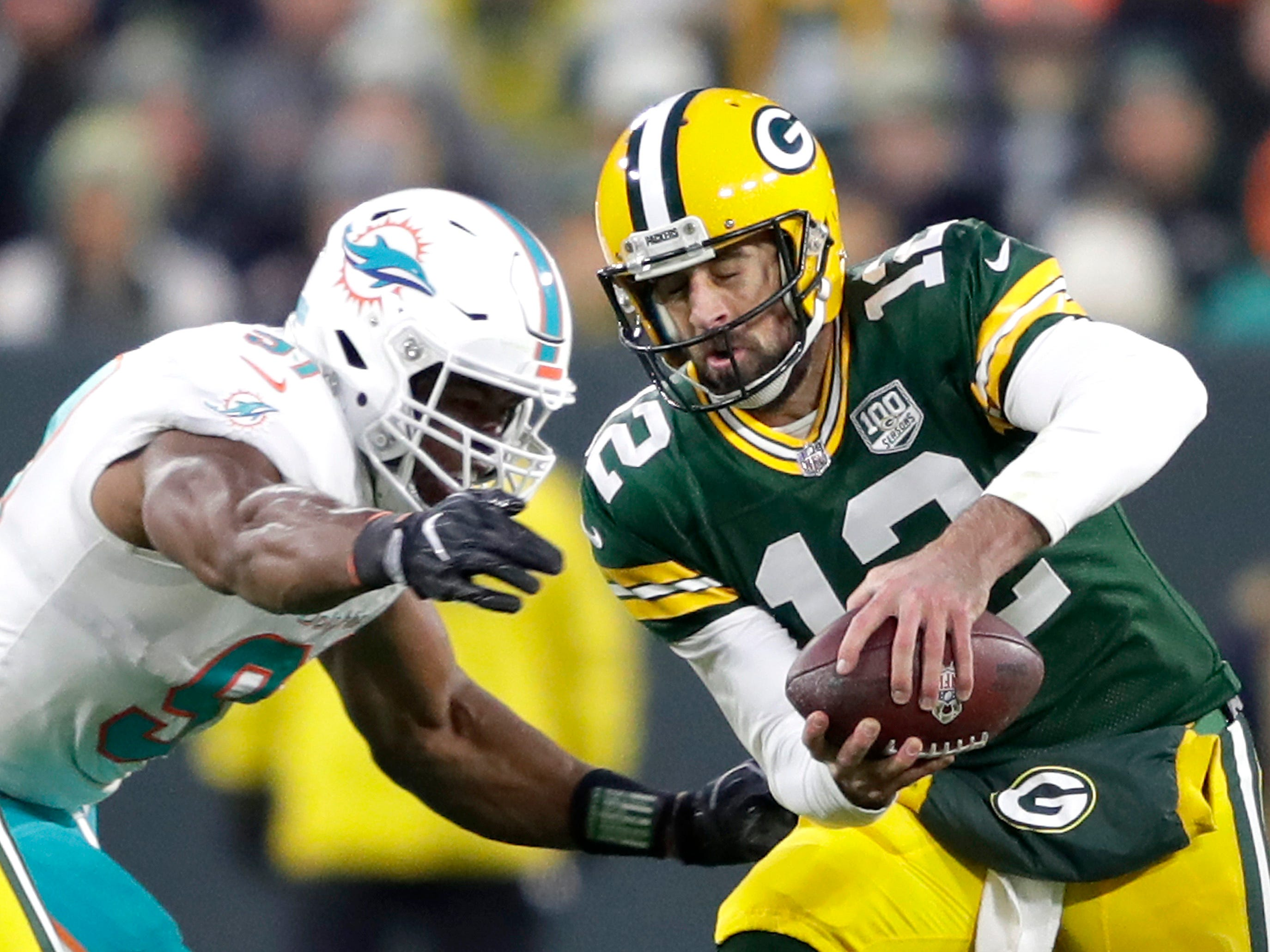 Green Bay Packers quarterback Aaron Rodgers is sacked by Miami Dolphins defensive end Cameron Wake in the first half of their football game on Sunday, November 11, 2018, at Lambeau Field in Green Bay, Wis.
