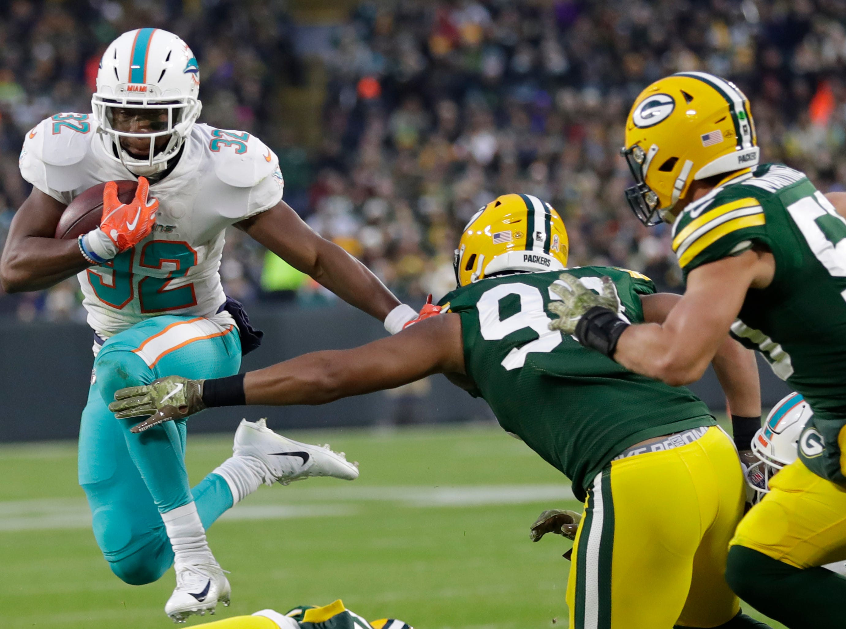 Miami Dolphins running back Kenyan Drake (32) dives for yardage against Green Bay Packers linebacker Reggie Gilbert (93) in the first half Sunday, November 11, 2018, Lambeau Field in Green Bay, Wis. 