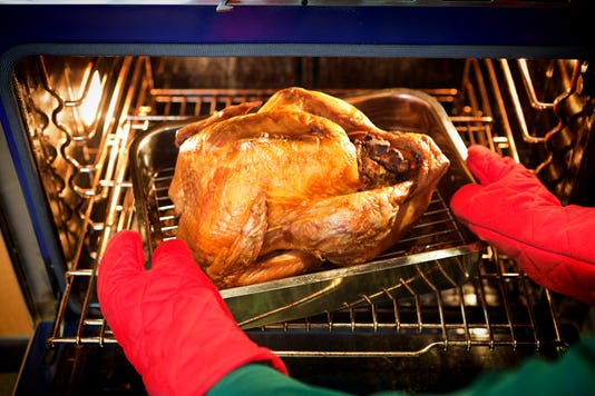 Roasting Thanksgiving Turkey With Stuffing In Oven
