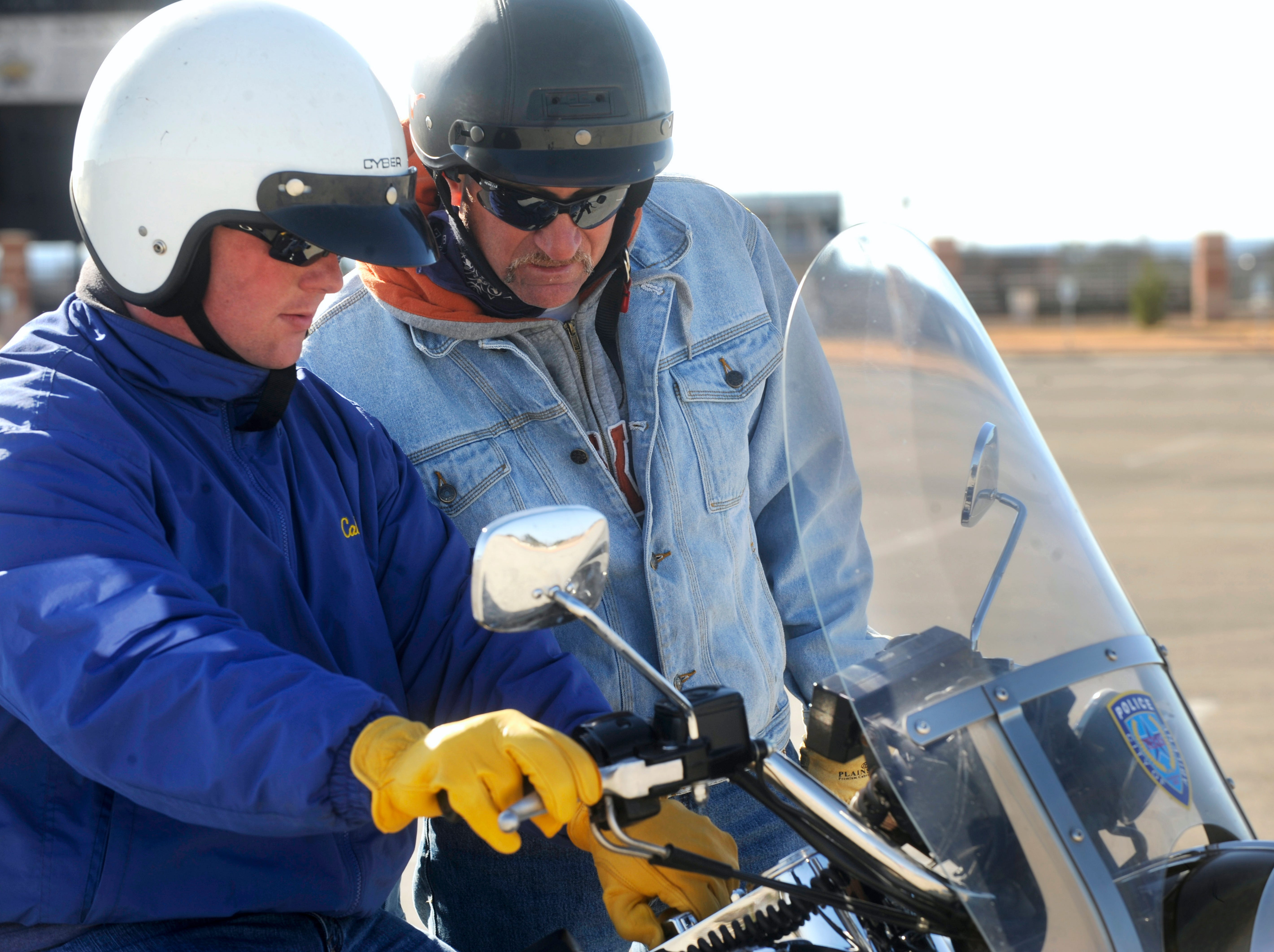 Rodney Holder, right, helps officer Tyson Kropp, new to the police motorcycle during training at the Shotwell Stadium parking lot Feb. 11, 2009.