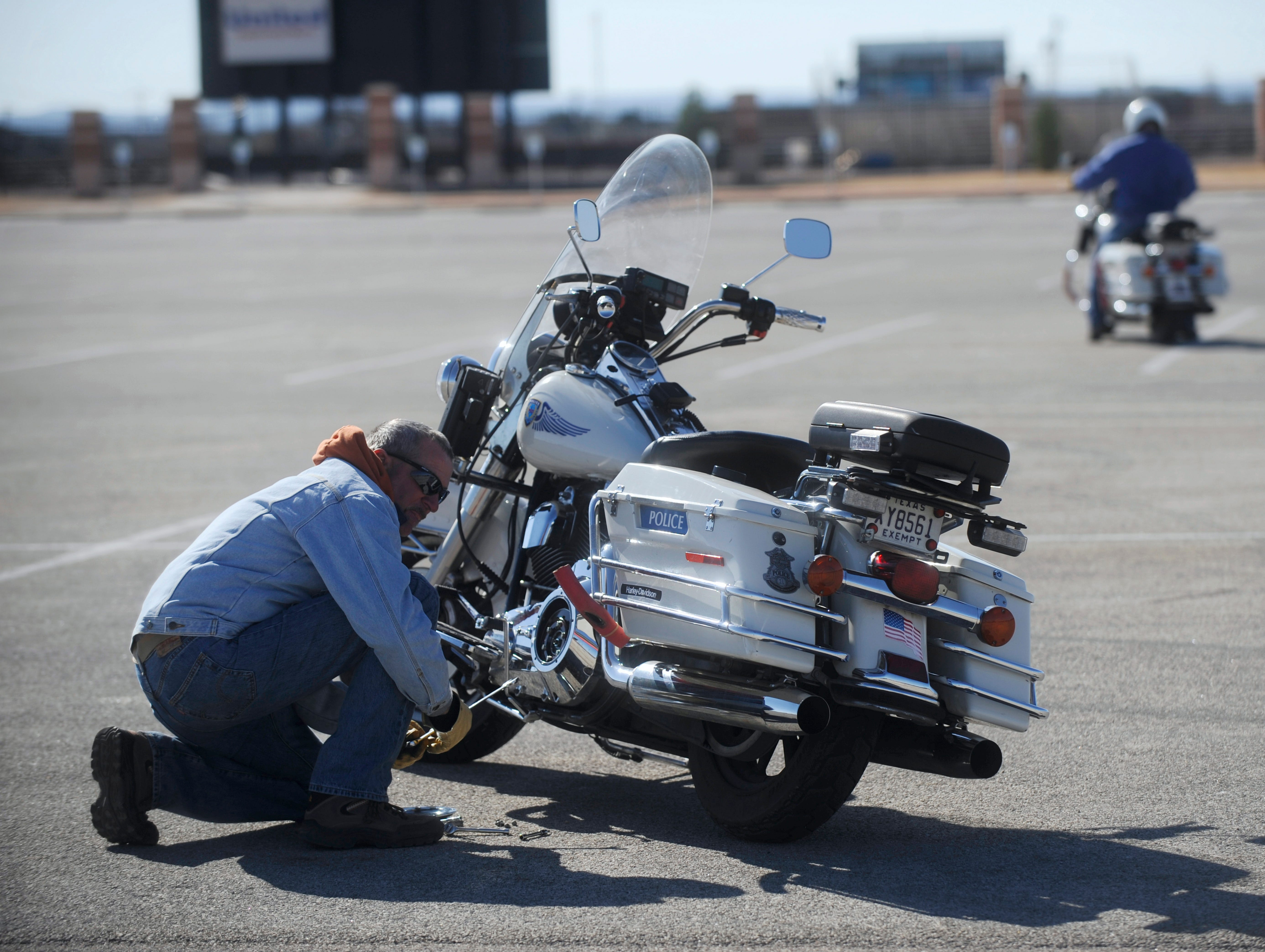 Rodney Holder, left, places rubber covering on the metal parts of the motorcycle closest to the ground during a tight turn before police motorcycle re-training at the Shotwell Stadium parking lot Feb. 11, 2009.