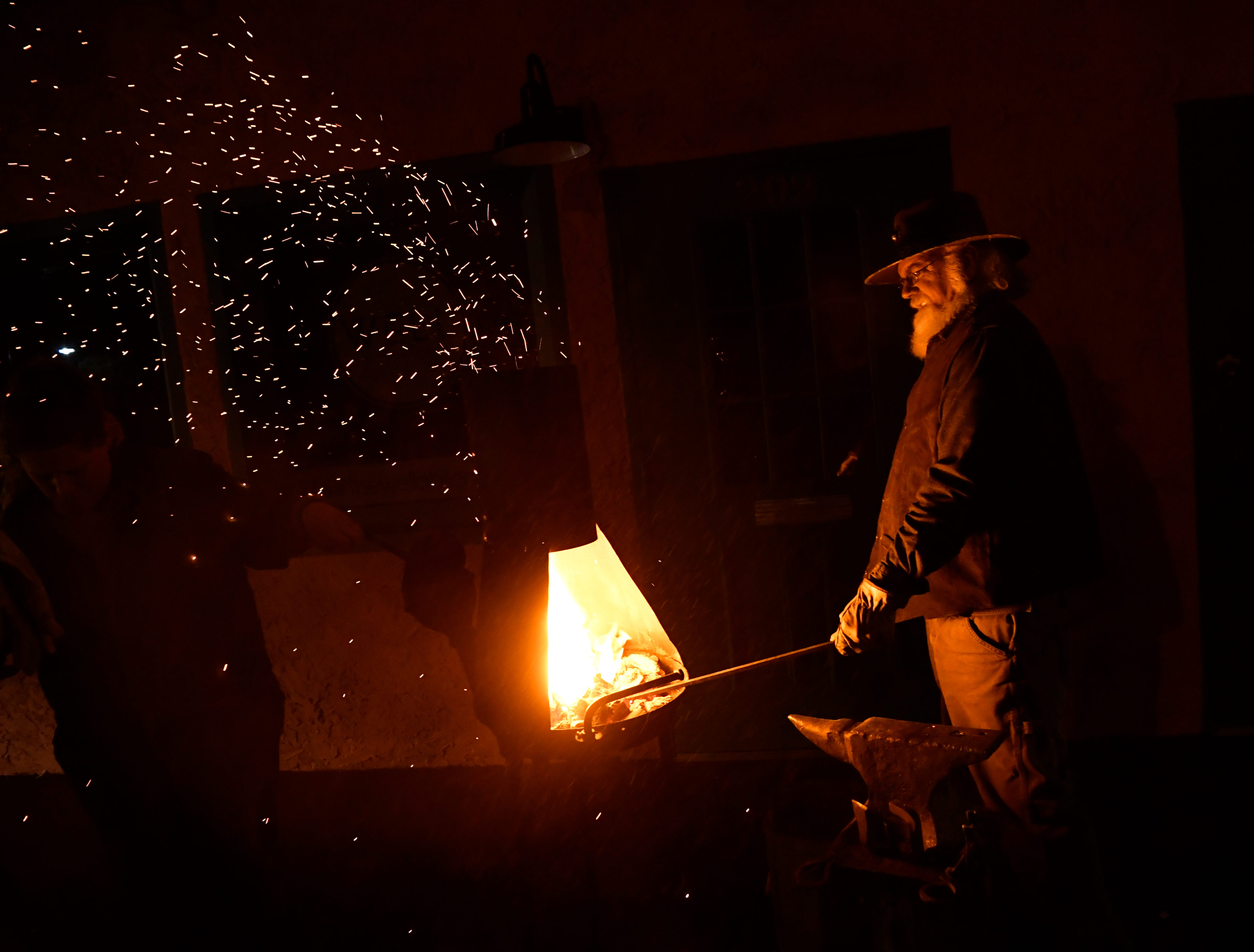 Sparks fly from the chimney of Michael Whitmore's portable forge during Thursday's ArtWalk. Whitmore teaches blacksmithing at his studio in Albany.