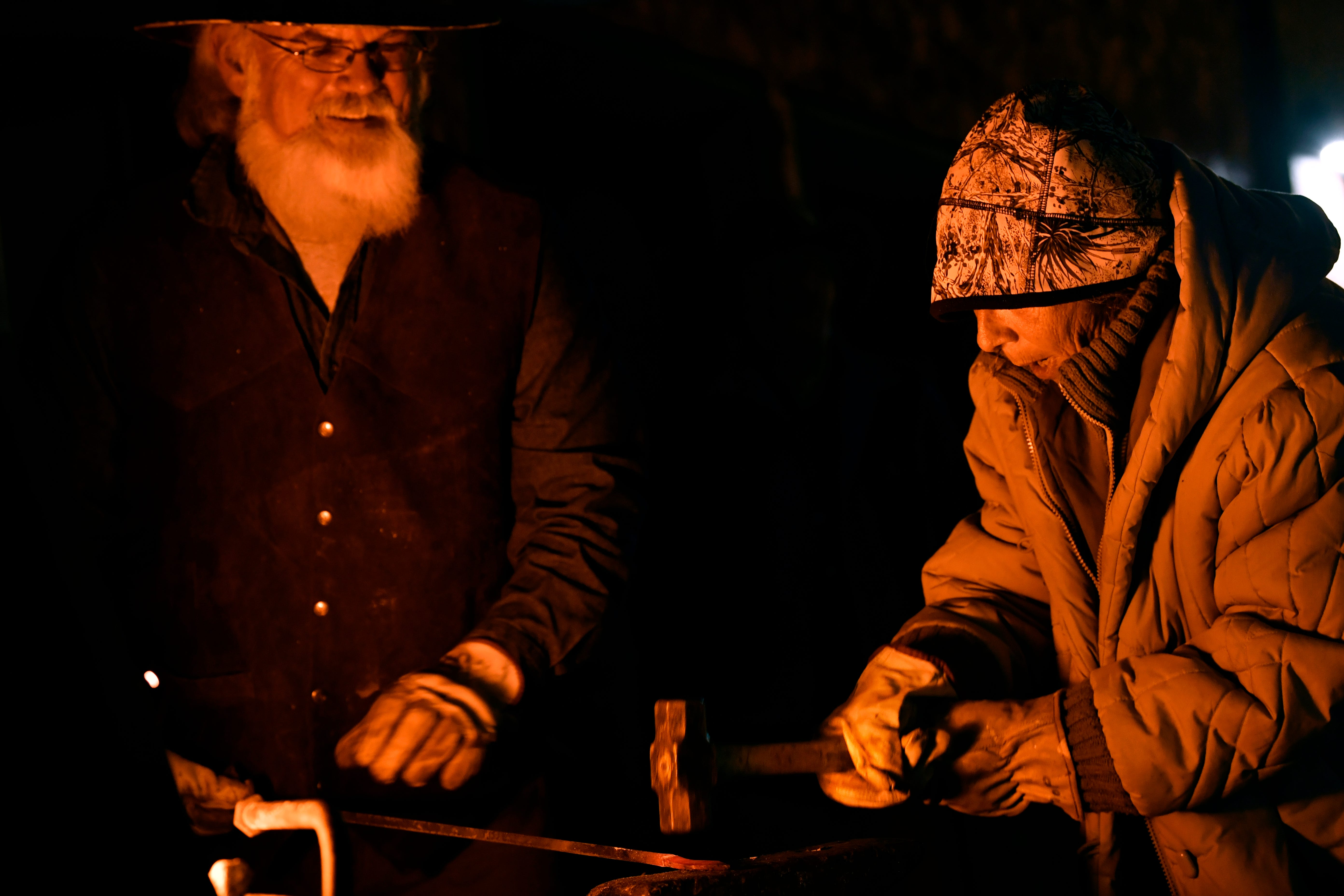Sharan Tate-Ambrosiani tries her hand at smithing as Michael Whitmore holds the steel for her in front of his portable forge at ArtWalk Thursday.