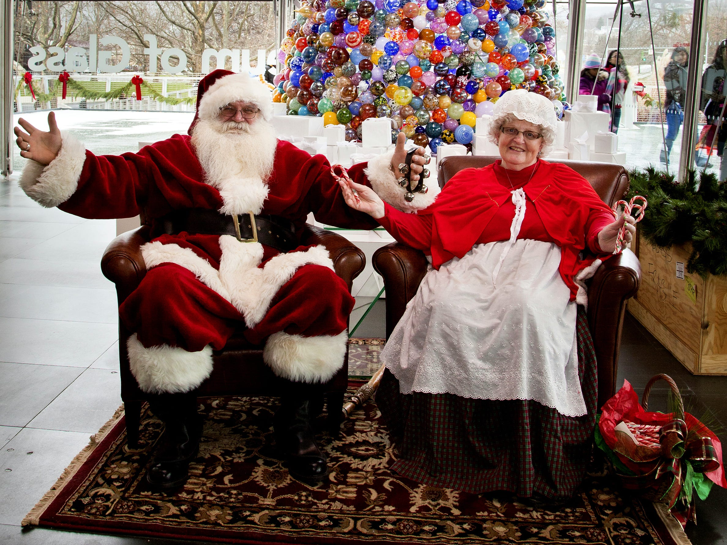 Santa and Mrs. Claus sit in front of the holiday ornament Christmas tree at the Corning Museum of Glass in 2015.