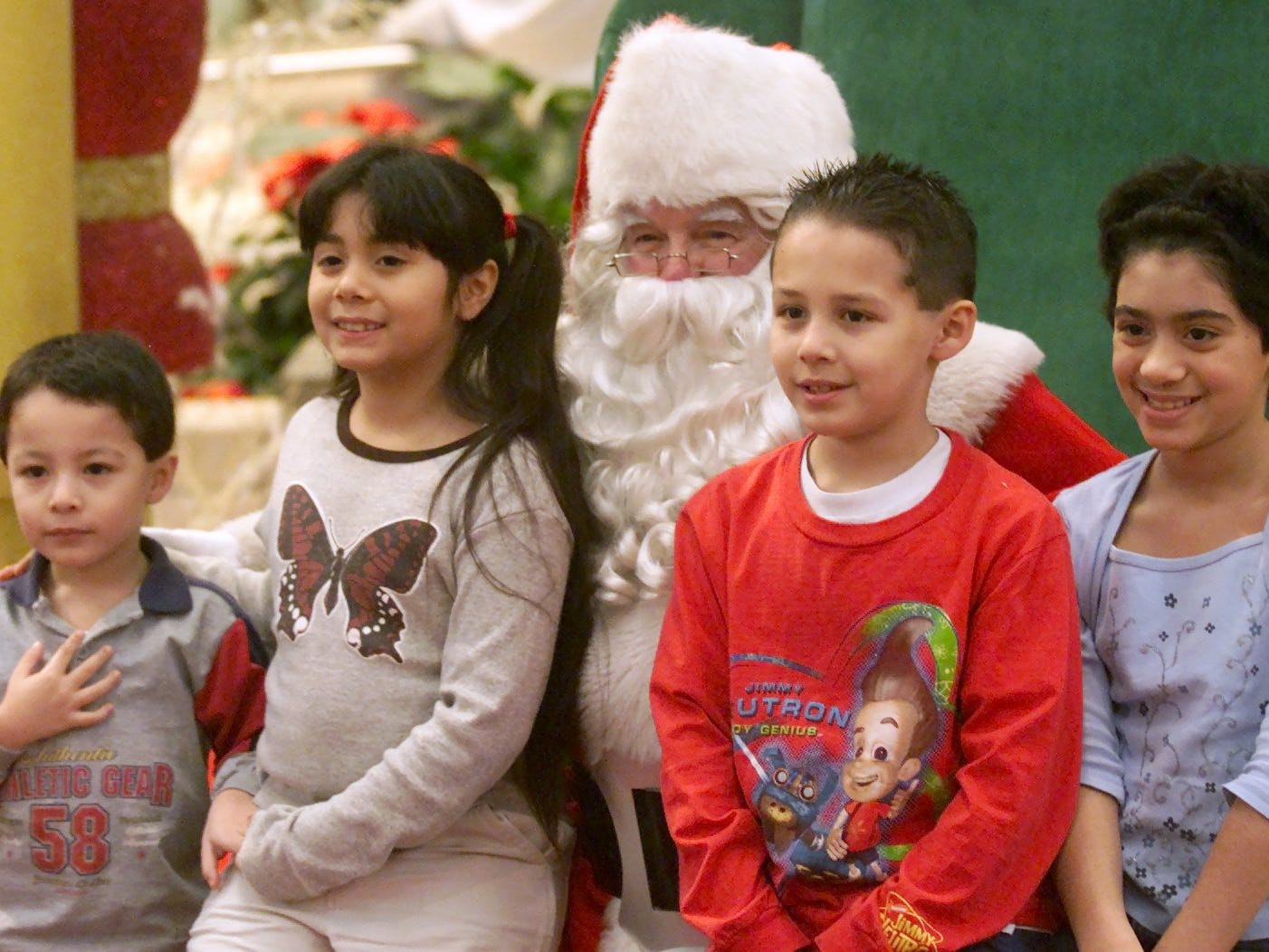 he children of the Tuyul family of Elmira, from left, Joshua, 3, Nicole, 8, Alex, 8, and Anastasia, 10, pose with Santa Clause on Monday at the mall in 2002.