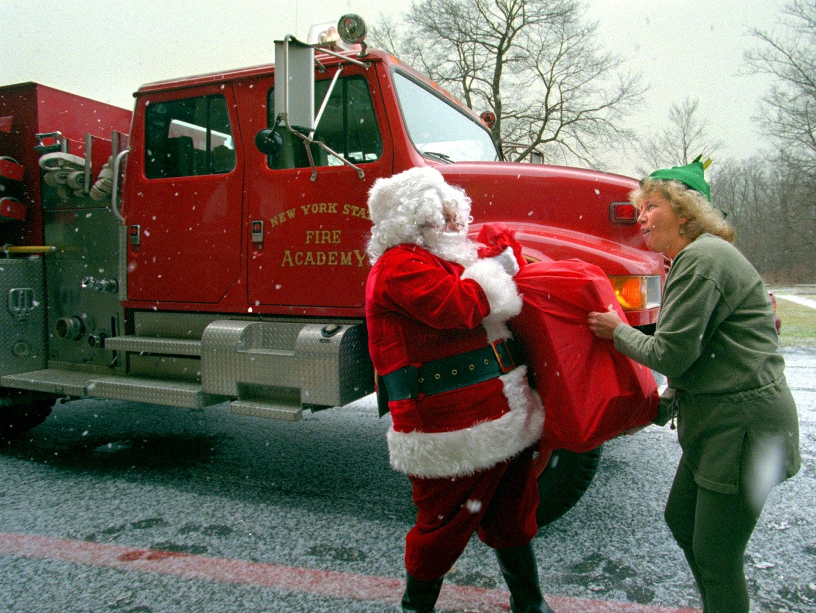 12/24/99; 4C:  A Christmas elf helps Santa Claus load toys onto a fire truck Thursday at the New York State Fire Academy in Montour Falls. Aided by the Academy, Santa delivered the toys and a Christmas meal to a needy Schuyler County family.