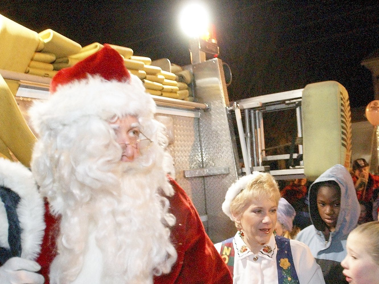 Santa Claus arrived Friday evening in downtown Trumansburg on the back of a firetruck during the annual Festival of Lights in 2003.