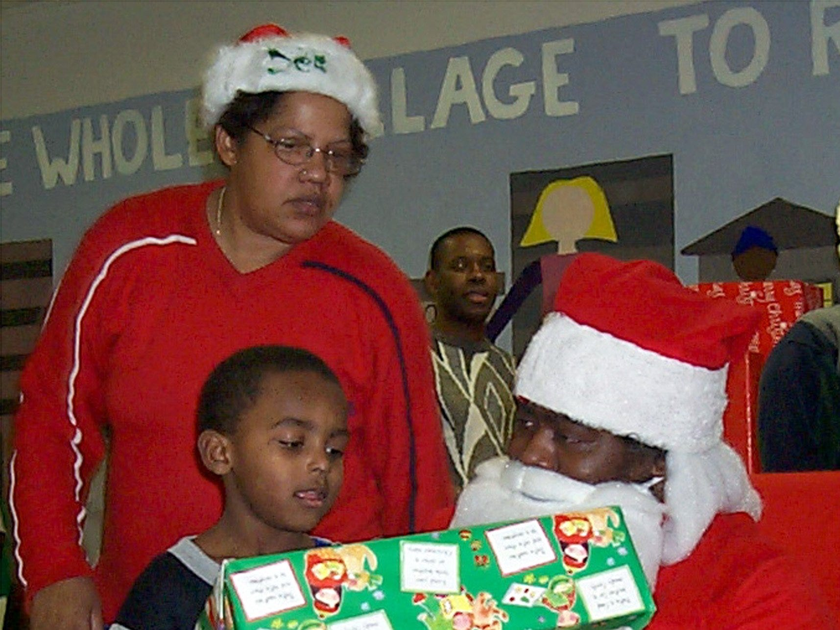 Santa Claus gives a gift to Robert Wilson, 3, of Elmira, on Saturday at the Ernie Davis Community Center's yearly Christmas Magic Party in 2000.