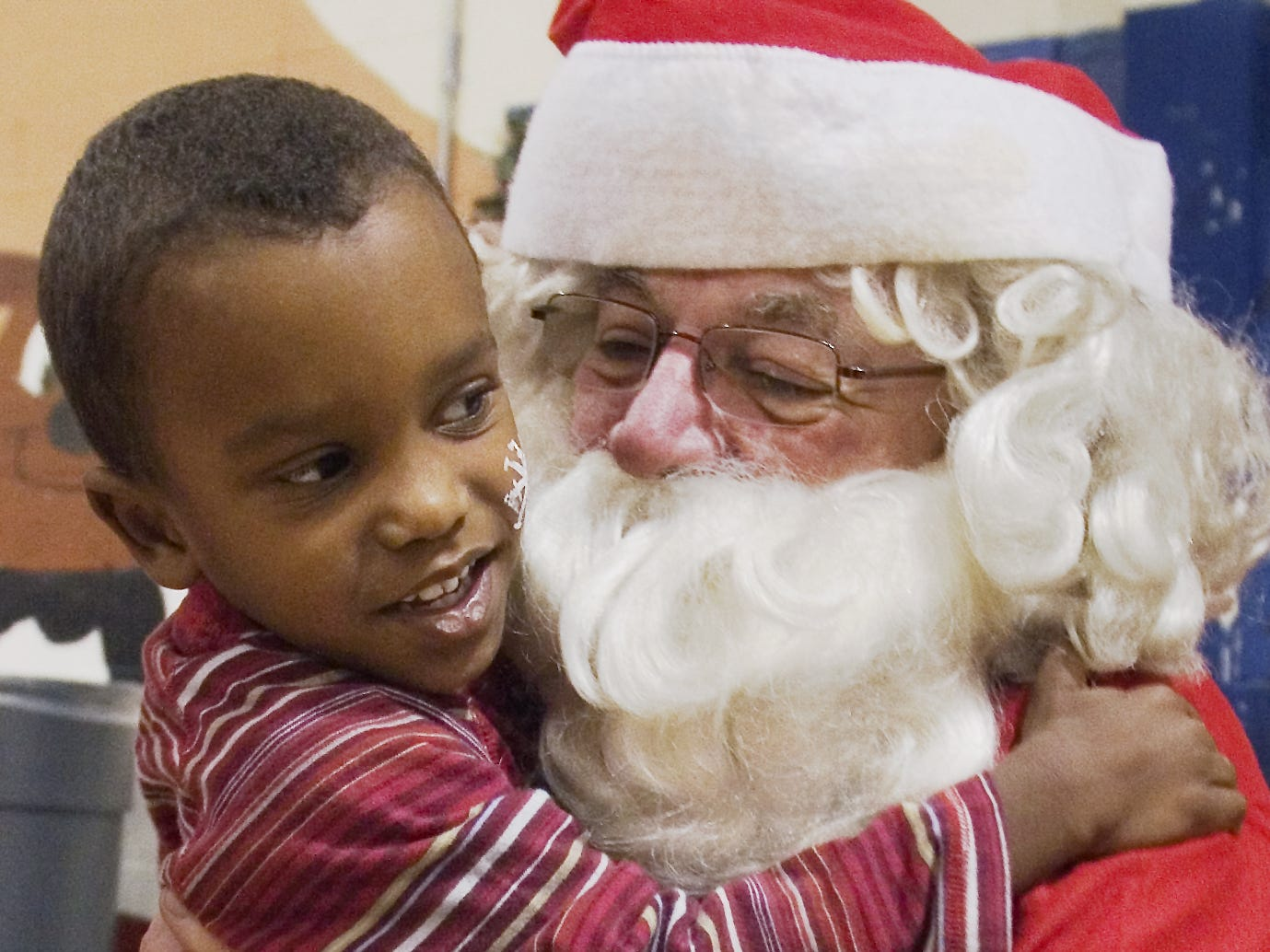 Kih Coleman, 4, of Elmira, hugs Santa during the Christmas party at the Ernie Davis Center in 2007.