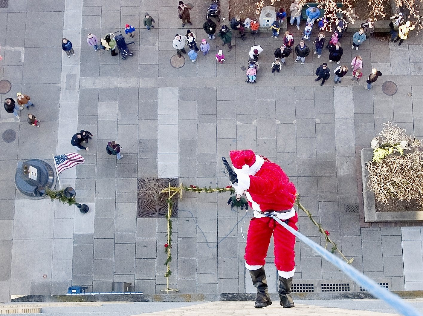 Mike Watkins, dressed as Santa Claus, waves to the crowd below as he rappels from the Bank of America Tower on the Ithaca Commons in 2004. Watkins is an Ithaca Police Department officer and SWAT team leader. The event kicked off Downtown Ithaca's Holidays Around the World celebration.
