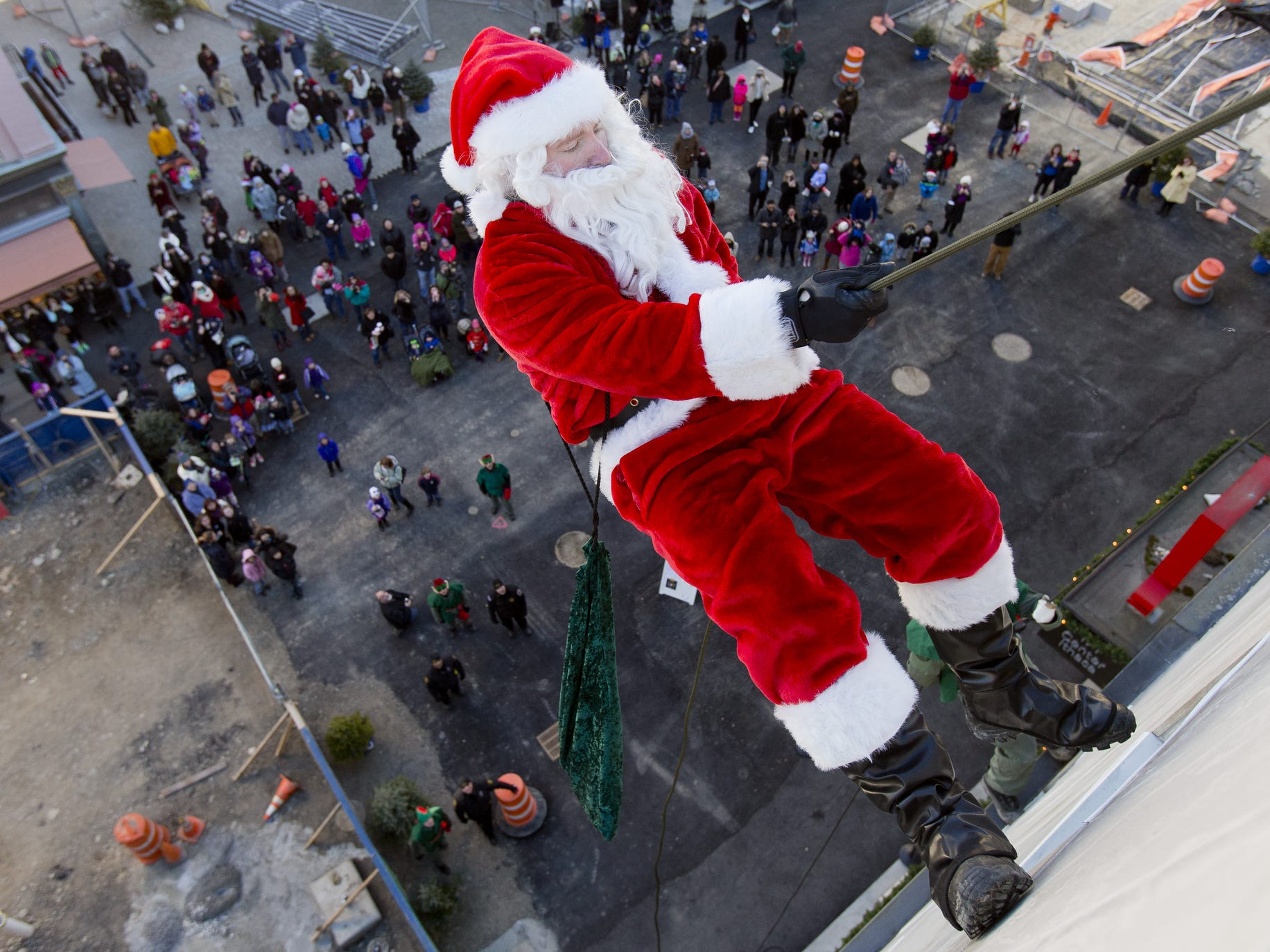 Santa, shown in 2014, annually rappels down the Center Ithaca building.