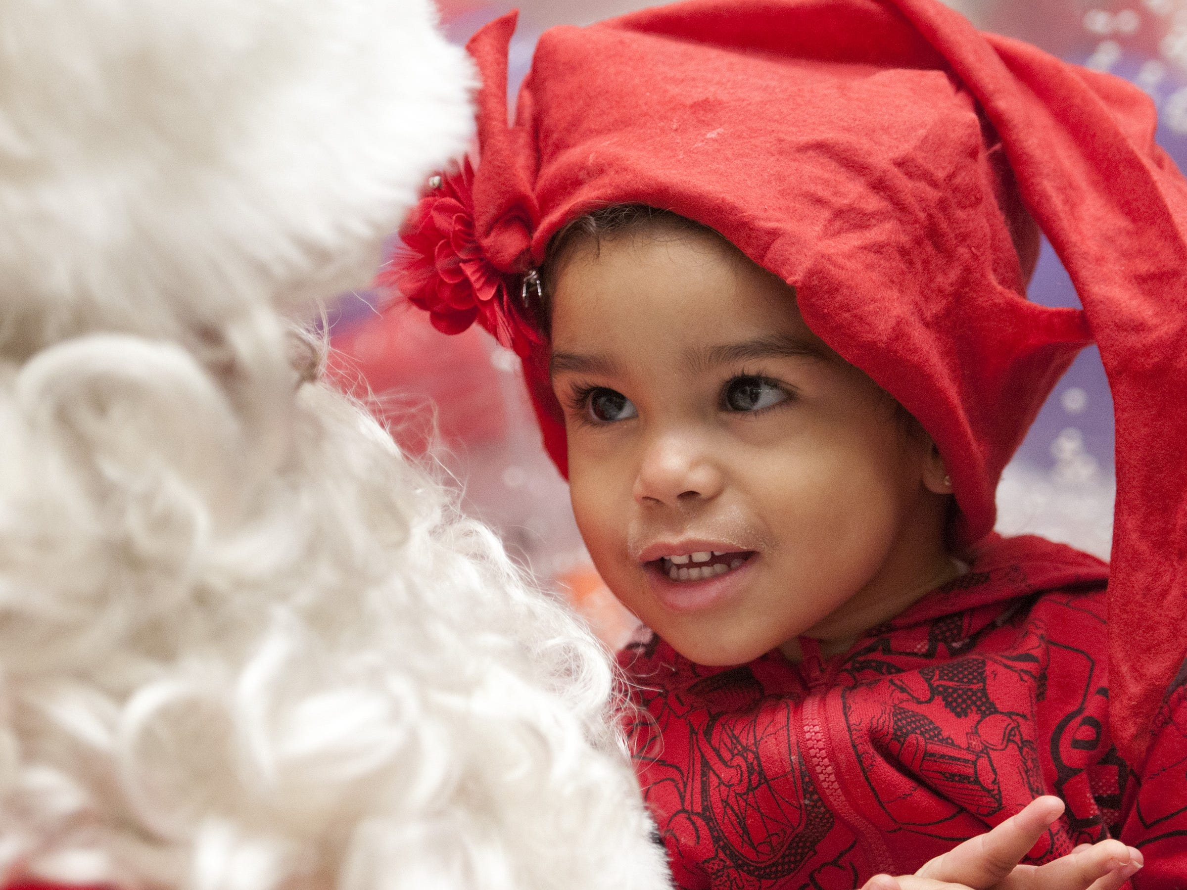 Gianna Williams, 2, from Ithaca, appears mesmerized by Santa in Center Ithaca in 2012.