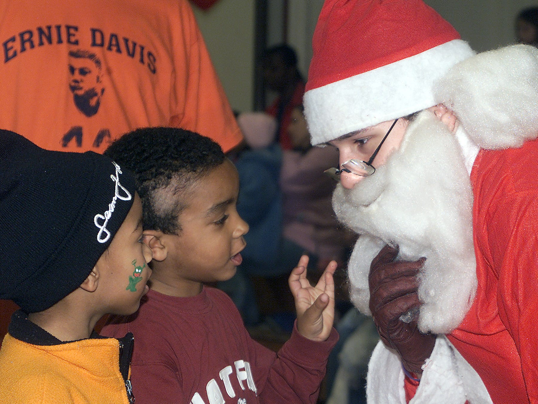 Santa Claus keeps a hold on his beard as he chats with Tai Wright Jr., left and Kaukakis Sessoms, both 5 and from Elmira, during the Christmas Magic party at the Ernie Davis Community Center in Elmira in 2005.