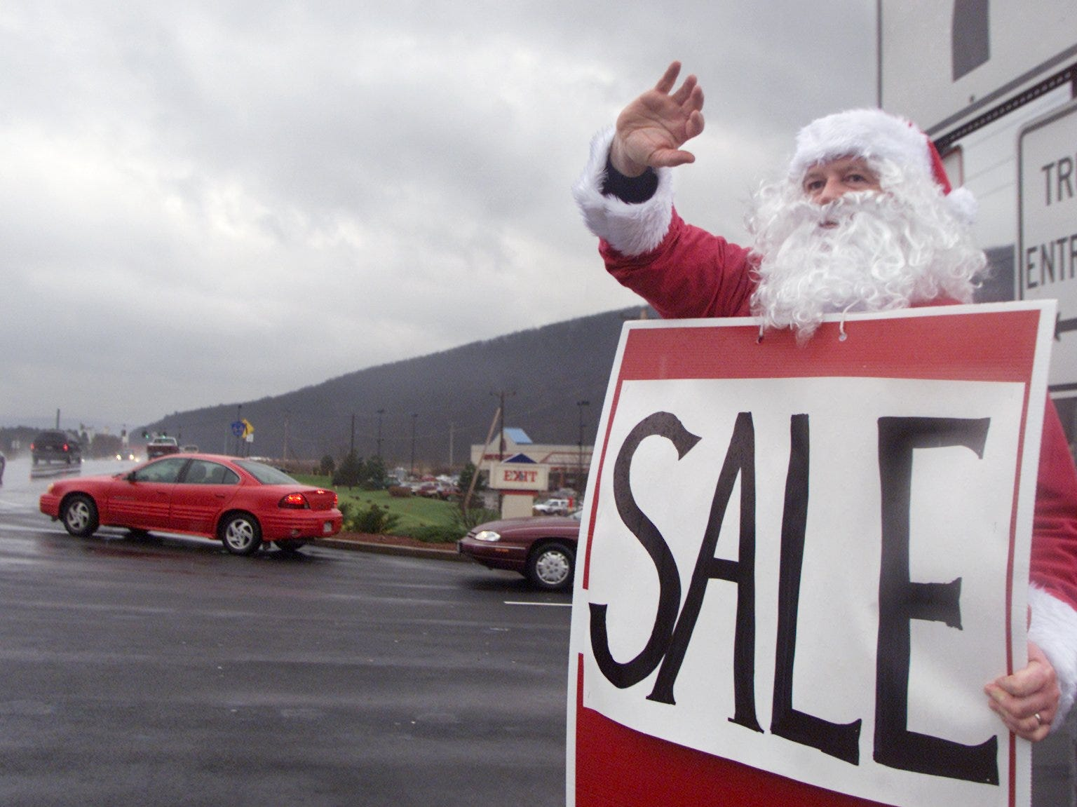 11/29/2003, 1C: Marty Chovanes of Troy, dressed as Santa Claus, waves to passers-by Friday afternoon at the entrance to Consumer Square in Big Flats, where he entices shoppers into Fashion Bug with a large sale billboard