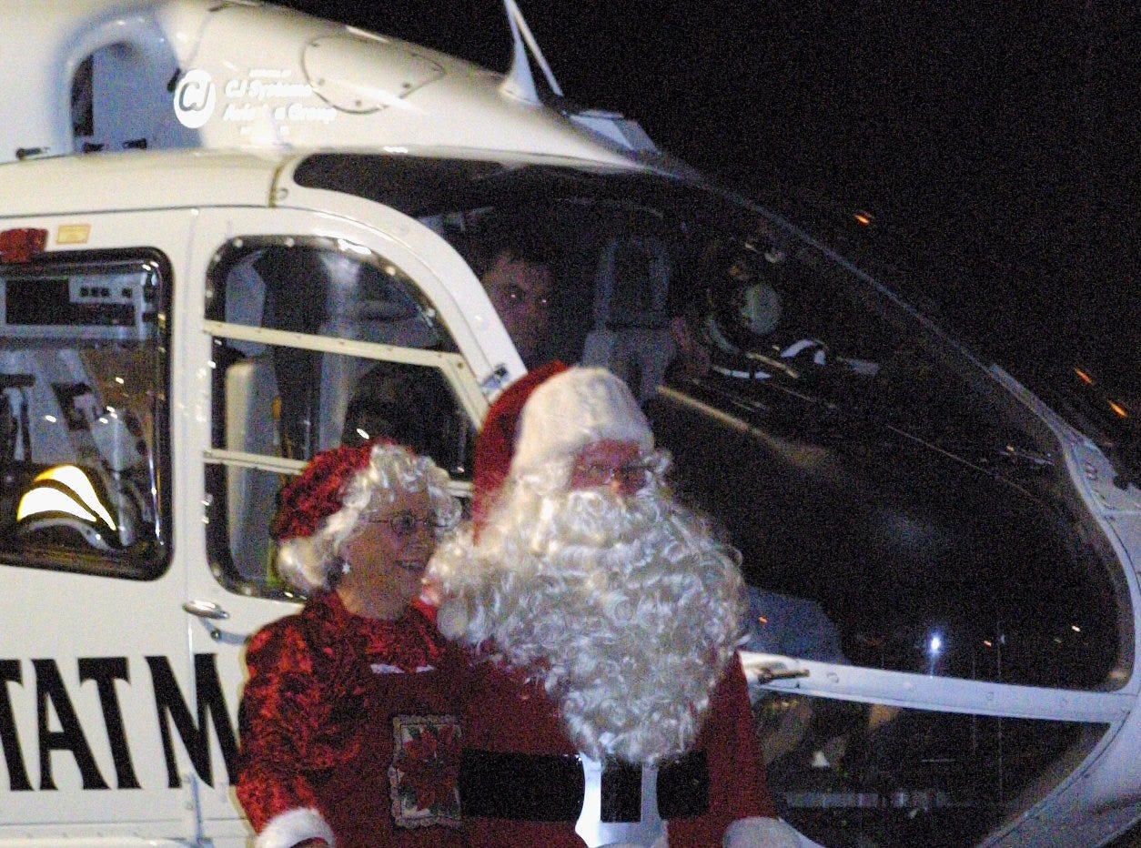 11/20/2004, 1A:   Santa and Mrs. Claus step onto the parking lot at Arnot Mall From a Guthrie MedEvac helicopter Friday evening.