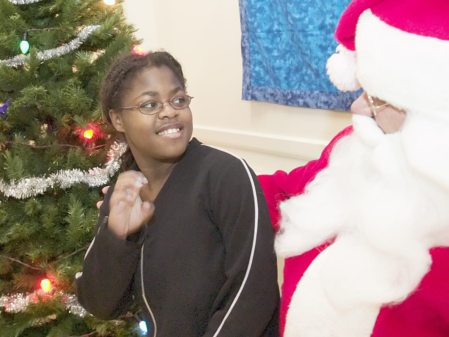MATTHEW HINTON / Journal Staff  Aziza Speight, 16, signs with Santa Claus, Charles Sundheimer, who is deaf, during a Christmas party especially for American Sign Language users, and for those wanting to learn in 2005. Though not deaf herself, Speight has a friend and a cousin who use sign language.