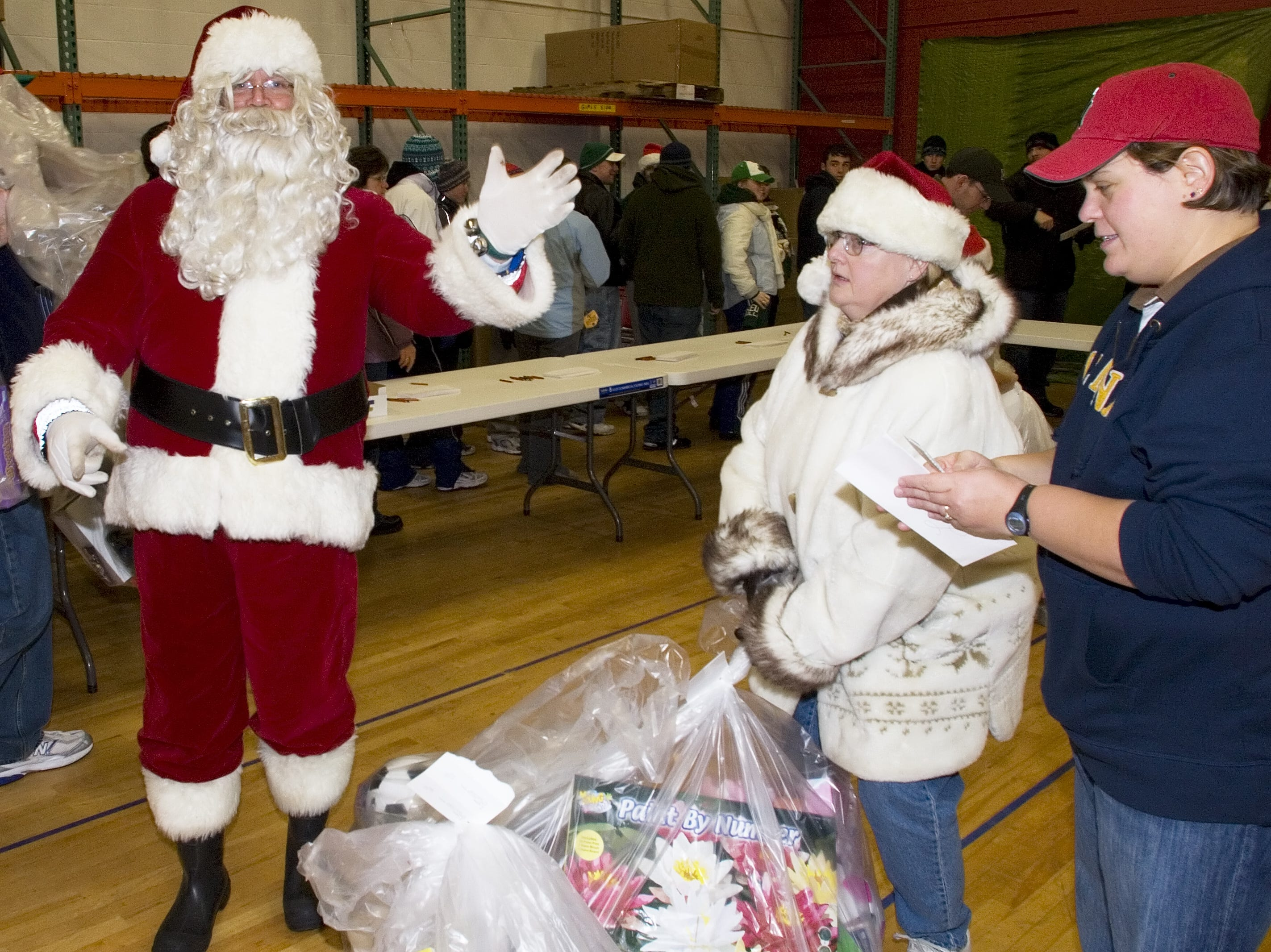 Jay Larrison of Elmira, dressed as Santa,  waves as an unidentified volunteer picks up a bag from Melissa Kalec, 36, of Elmira, right, in 2007.