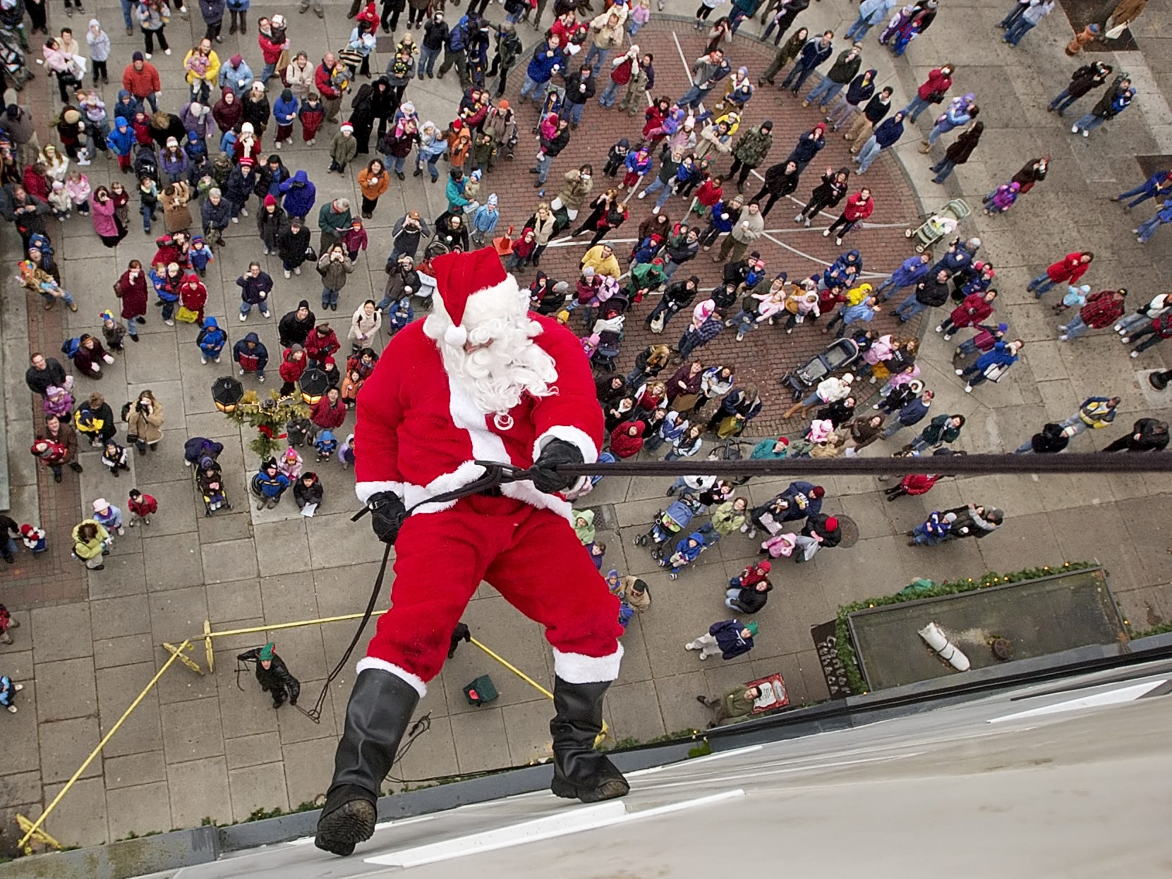 Ithaca Police Sgt. Mike Watkins, dressed as Santa Claus, rappels from the roof of Center Ithaca in 2006 as part of the Downtown Ithaca Holiday Parade of Ice Celebration. Santa's elves, which included members of the SWAT team composed of Ithaca Police Dept. and Tompkins County Sheriffs' Office personnel, also rappelled down the building.