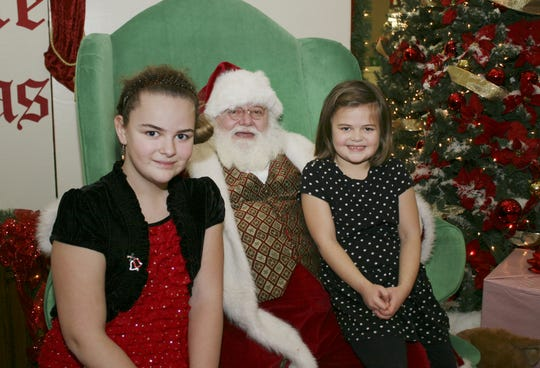 "In 2013, Emily Howland, 10, left, of Dryden, visited with Santa at the Shops at Ithaca Mall with her sister, Sara, 6. They both said they want dolls from Disney's ""Frozen"" movie."