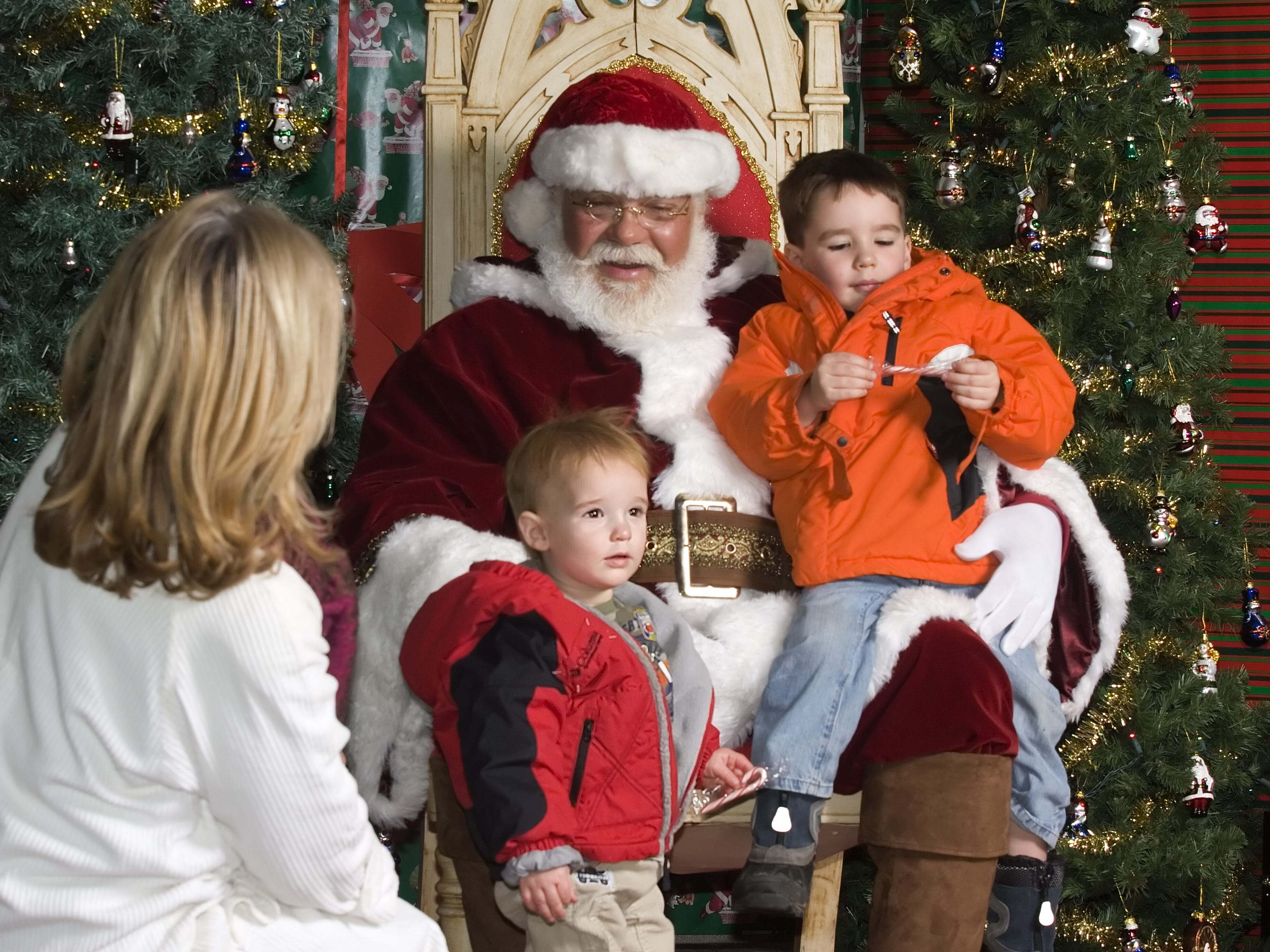 NEED YEAR Joy Brewer, 53, left, talks to her grandsons Nolan Brewer, 1, and Alden Brewer, 3, both of Elmira, as they pose for a photograph with Santa Claus on Friday at 109 North Main Street in Elmira. The Elmira-based photo studio LaVere Media offered photos with Santa after the parade.