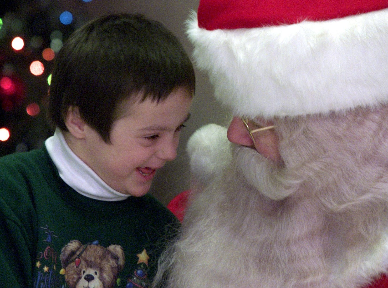 22.12.2000, 1A:  Zachary Hackett, 9, of Horseheads meets Santa Claus, portrayed by Bill Connelly, on Saturday at the Elmira Heights Fire Department.