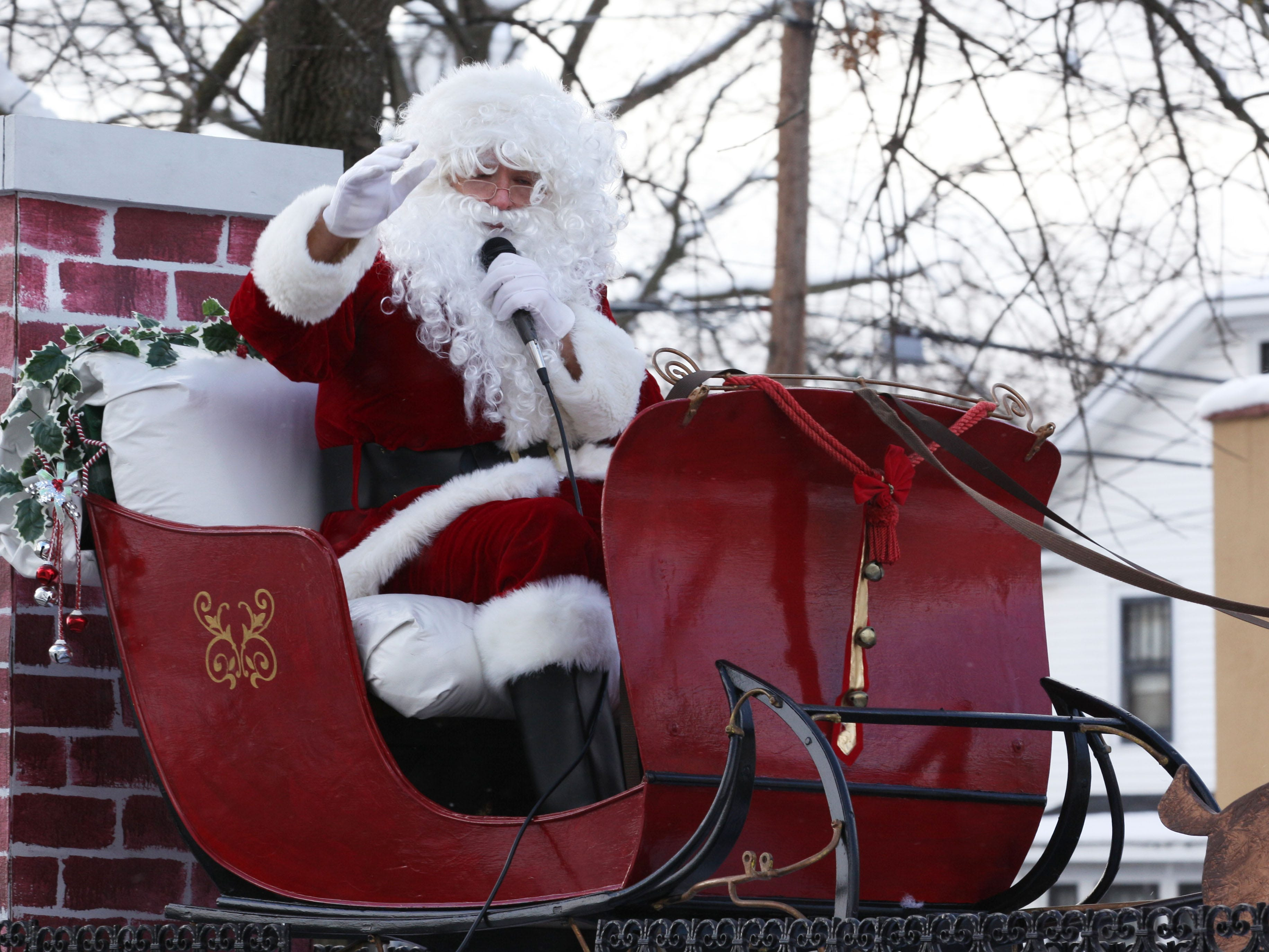 Santa waves from the Downtown Elmira Holiday Parade on Friday on College Avenue in 2014.