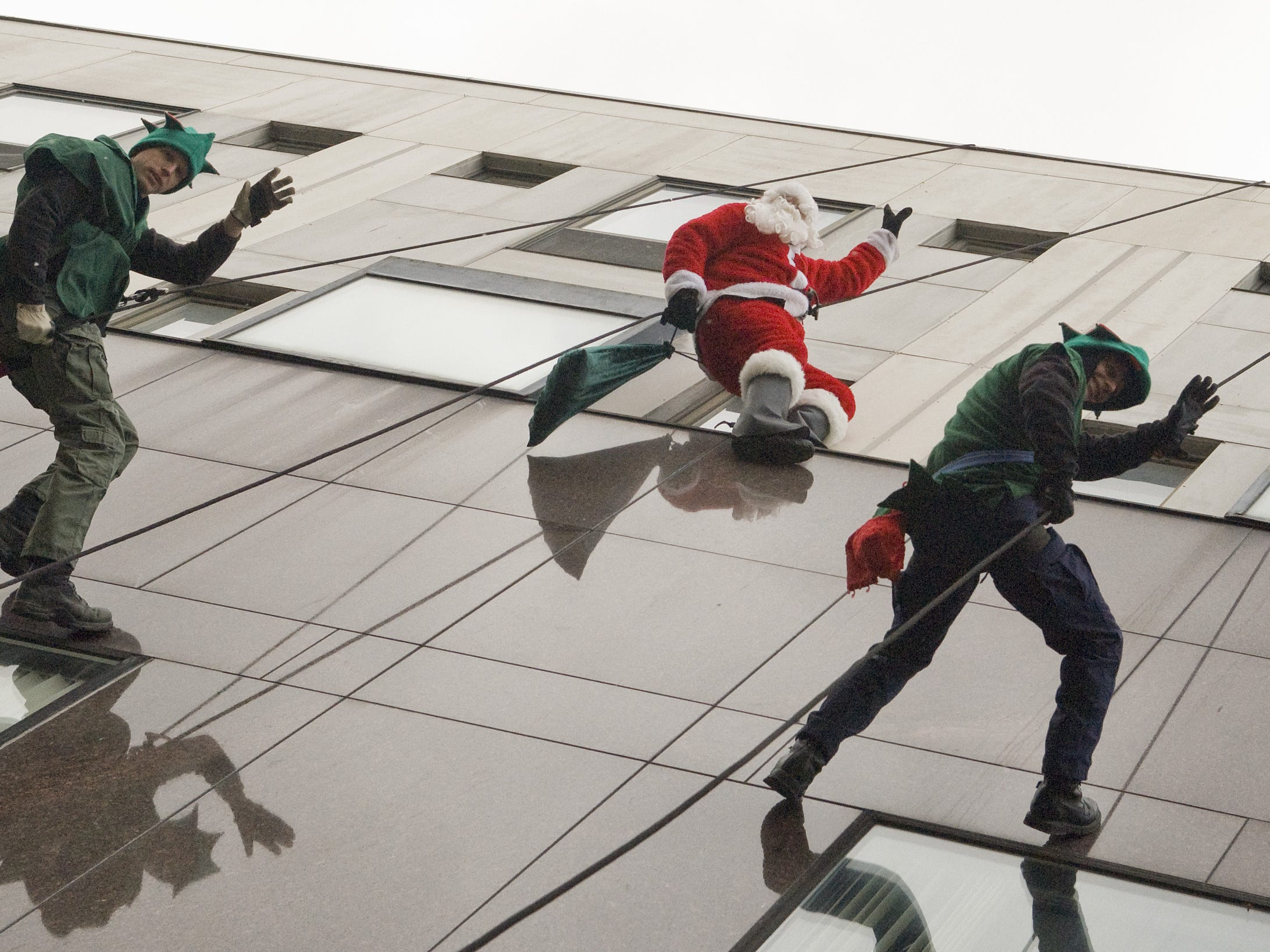 Dozens of kids young and old gaze up and watch Santa rappel down from the roof of Center Ithaca in 2010. Santa and two of his elves flew in for the festivities which included music by Johnny Russo and his band, ginger bread house creations and a dance and choral recital.