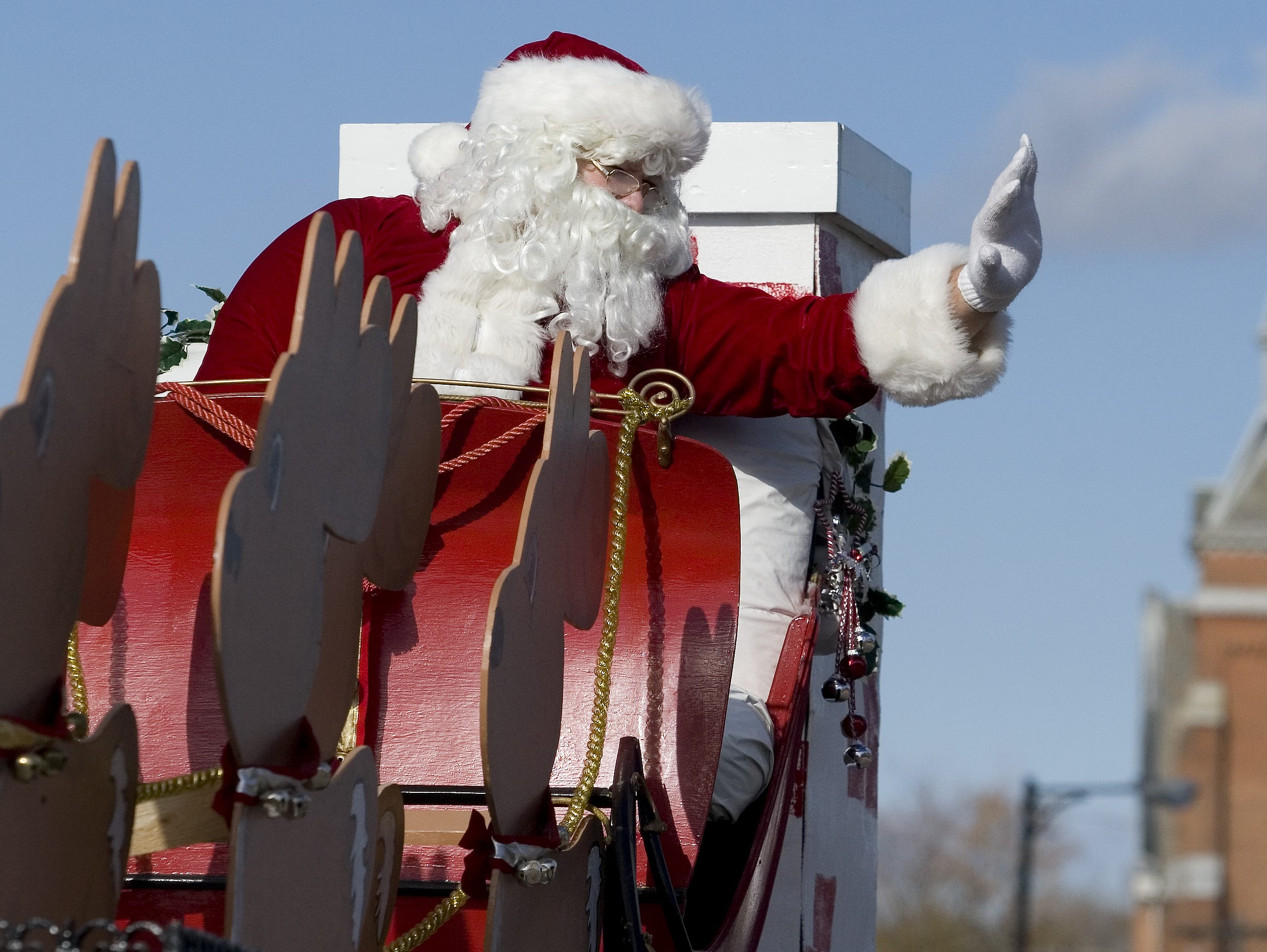 Santa Claus, whose float is bringing up the rear of the parade, waves to spectators lining North Main Street in 2007.