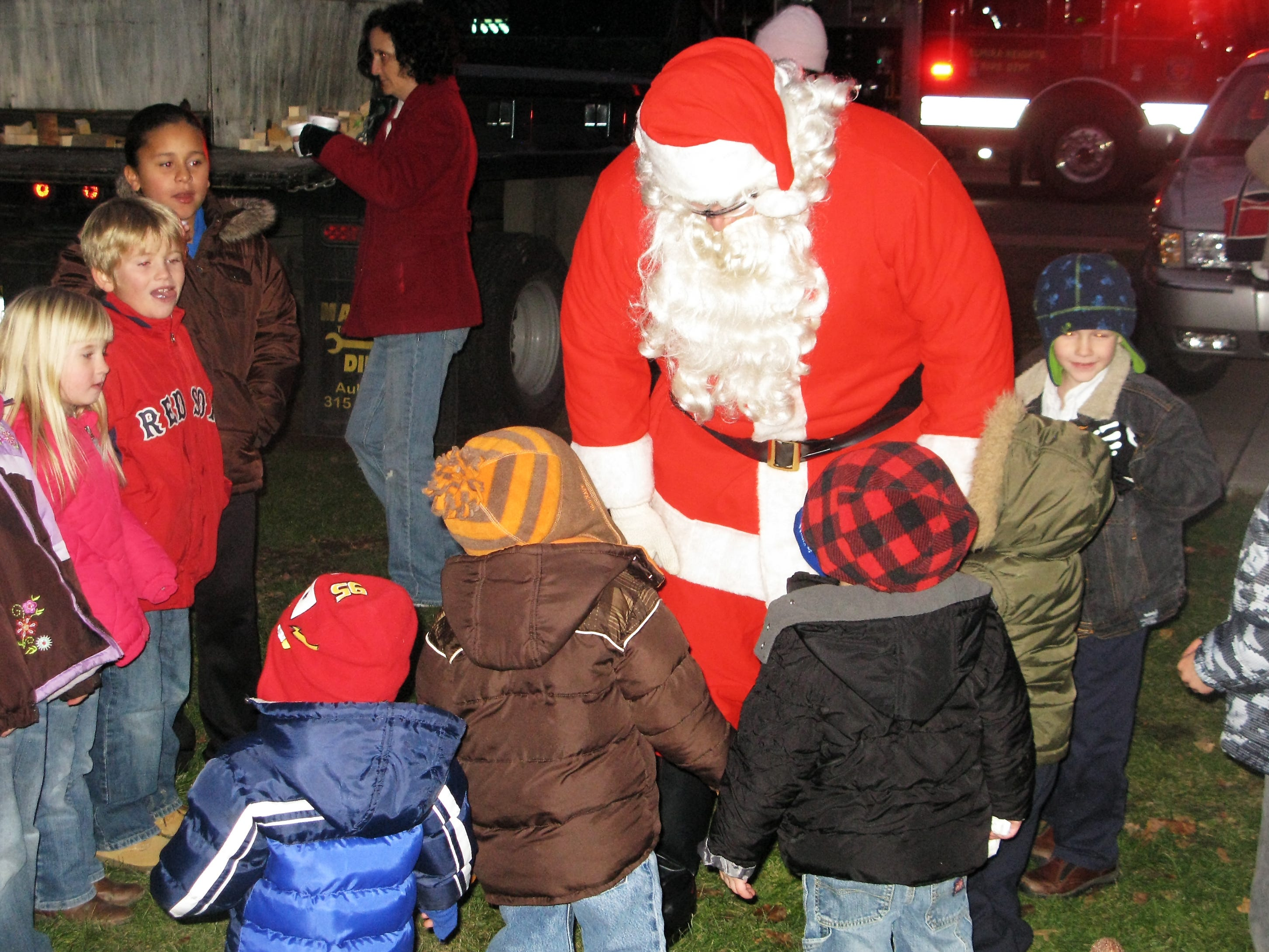 Santa Claus is surrounded by children as he arrives at Oakwood Park in Elmira Heights for the 2010 Lights in the Heights festival.