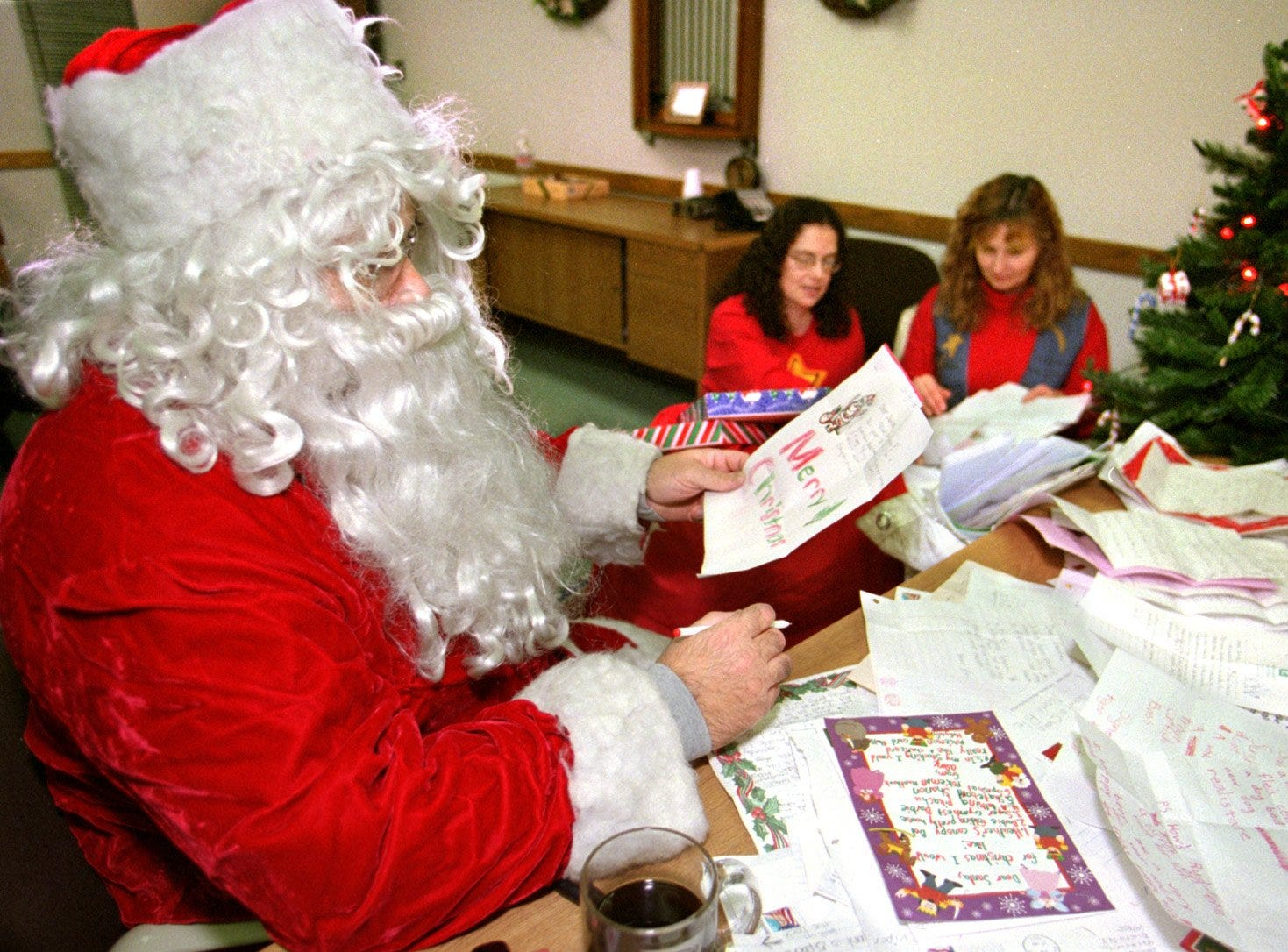 12,19,99; 1A:  Santa Claus pours through thousands of letters from children while his helpers from the Elmira Post Office sort though his mail bags Wednesday.