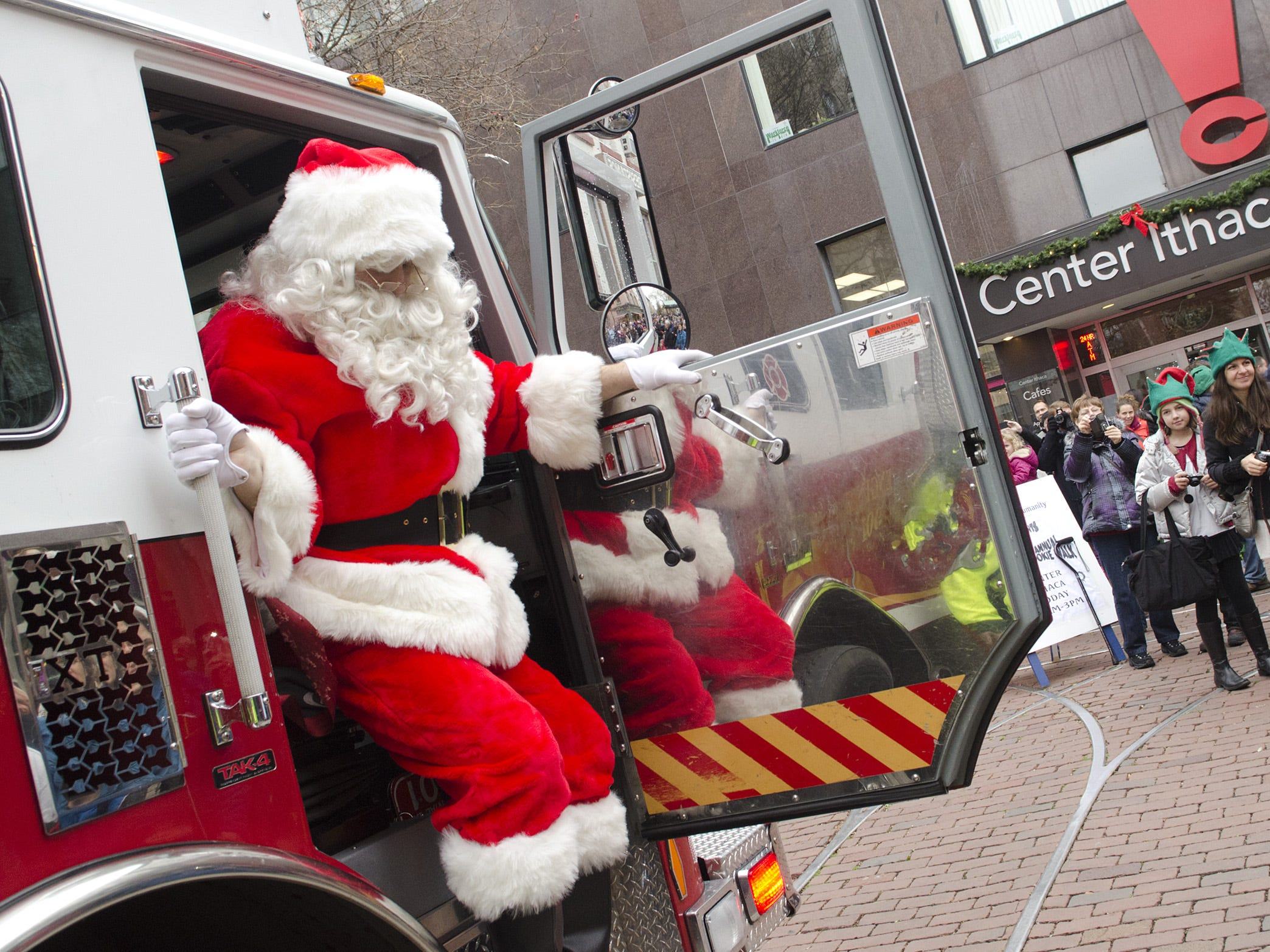 Santa Claus hops off of a fire truck Sunday on The Commons. Santa?s arrival ushered in the start of the Downtown Winter Festival in 2012.