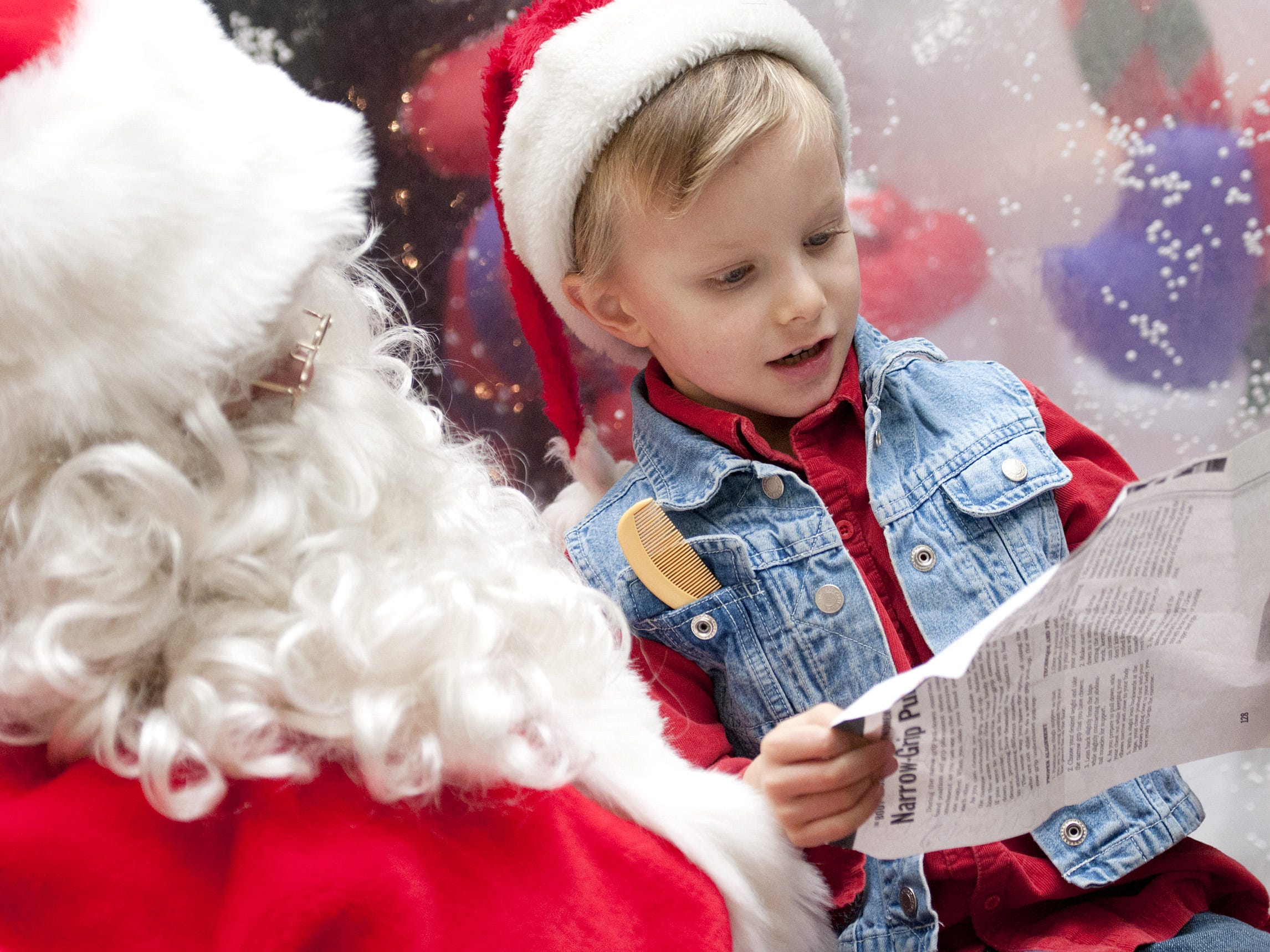 Auggie Doria, 6, from Ithaca, reads Santa his wish list for Christmas in 2012 at the Downtown Winter Festival in Ithaca.