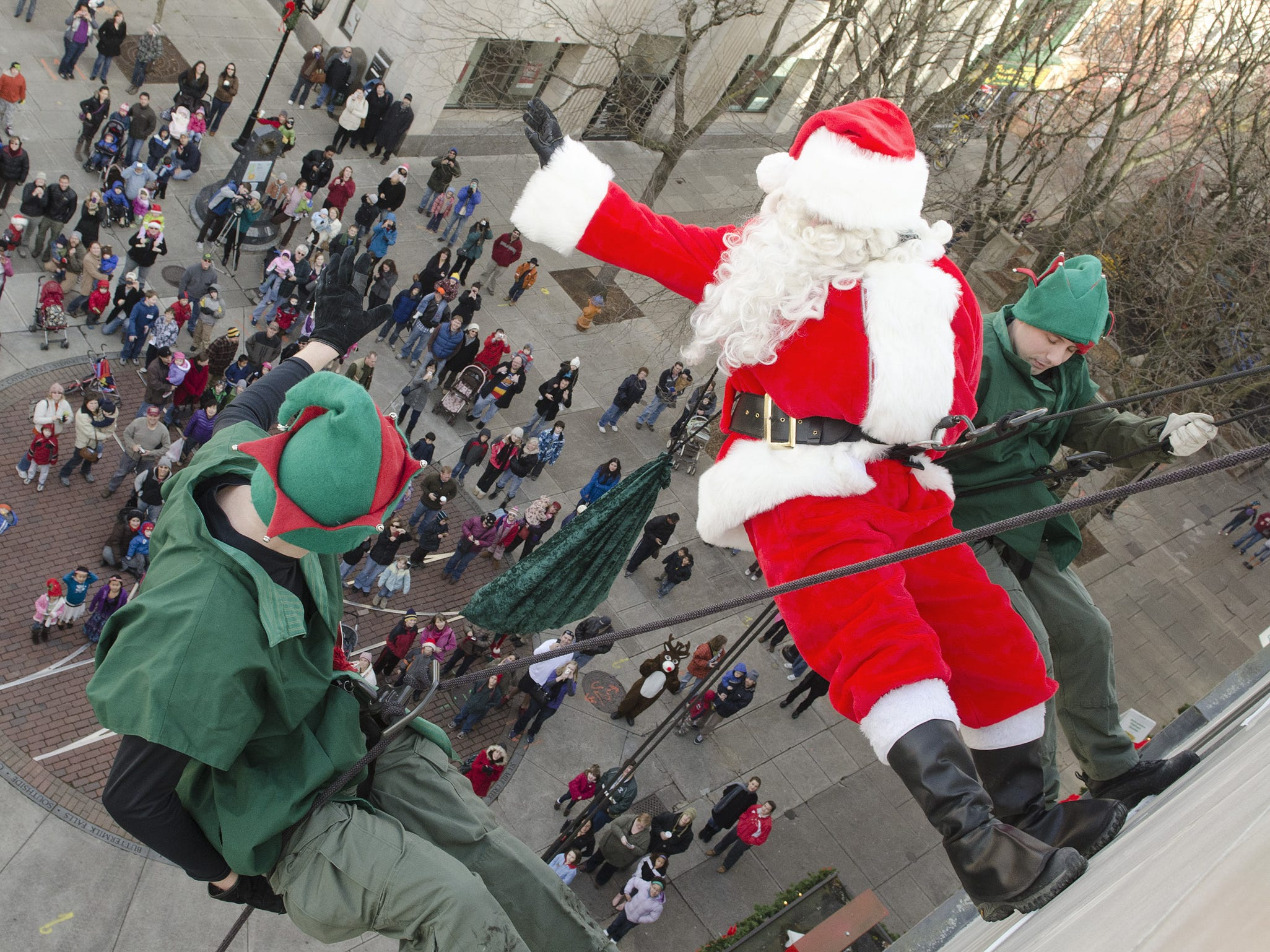 Santa and his elves rappel down Center Ithaca to an awaiting crowd on the Commons in 2011.