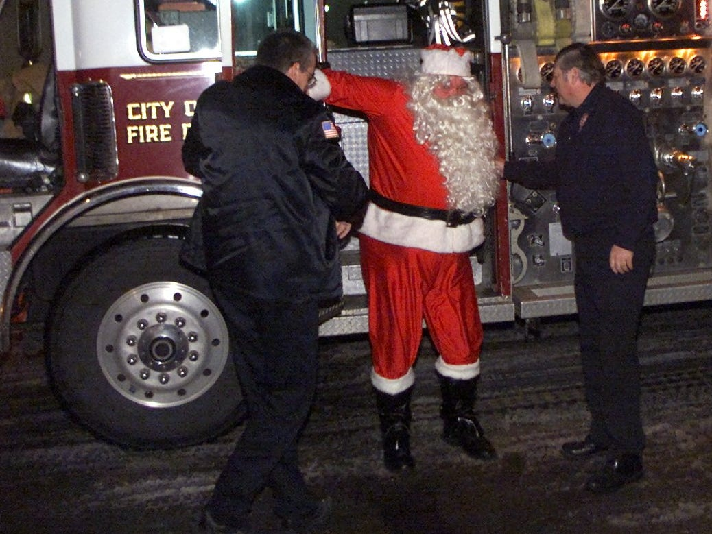 Santa Claus steps off a firetruck with help from Corning city firefighter Rick Thorne, left, and Lt. Paul Card during a tree-lighting ceremony Thursday at the Marconi Lodge on West Pulteney Street in 2002.