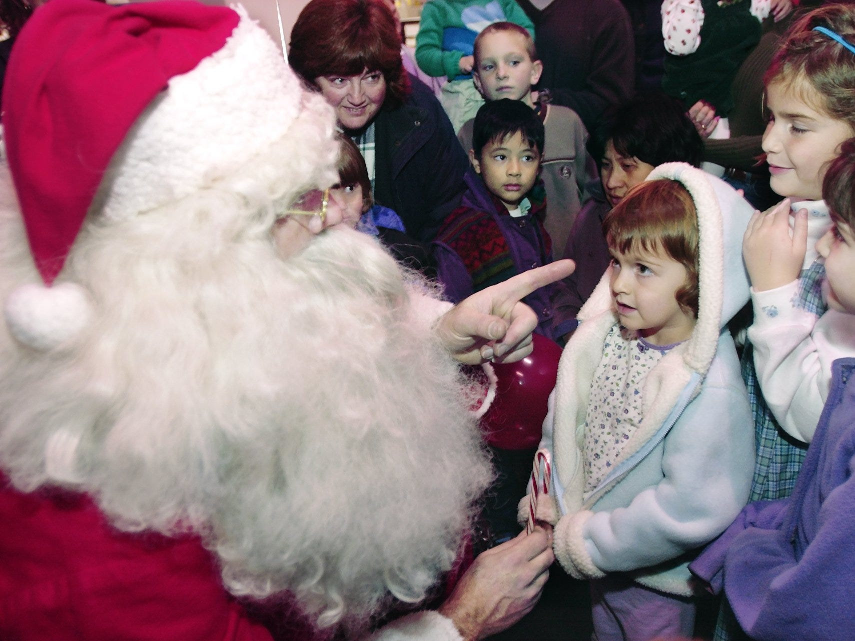 Before getting their candy canes, sisters Casey, 6, right, Erin, 8, and Bridget Futsko, 3, ask Santa Claus for a trampoline for Christmas in Center Ithaca in 2001. Santa Claus arrived at the Commons on an Ithaca Fire Department fire truck, instead of his usual reindeer, to open up the holiday season.