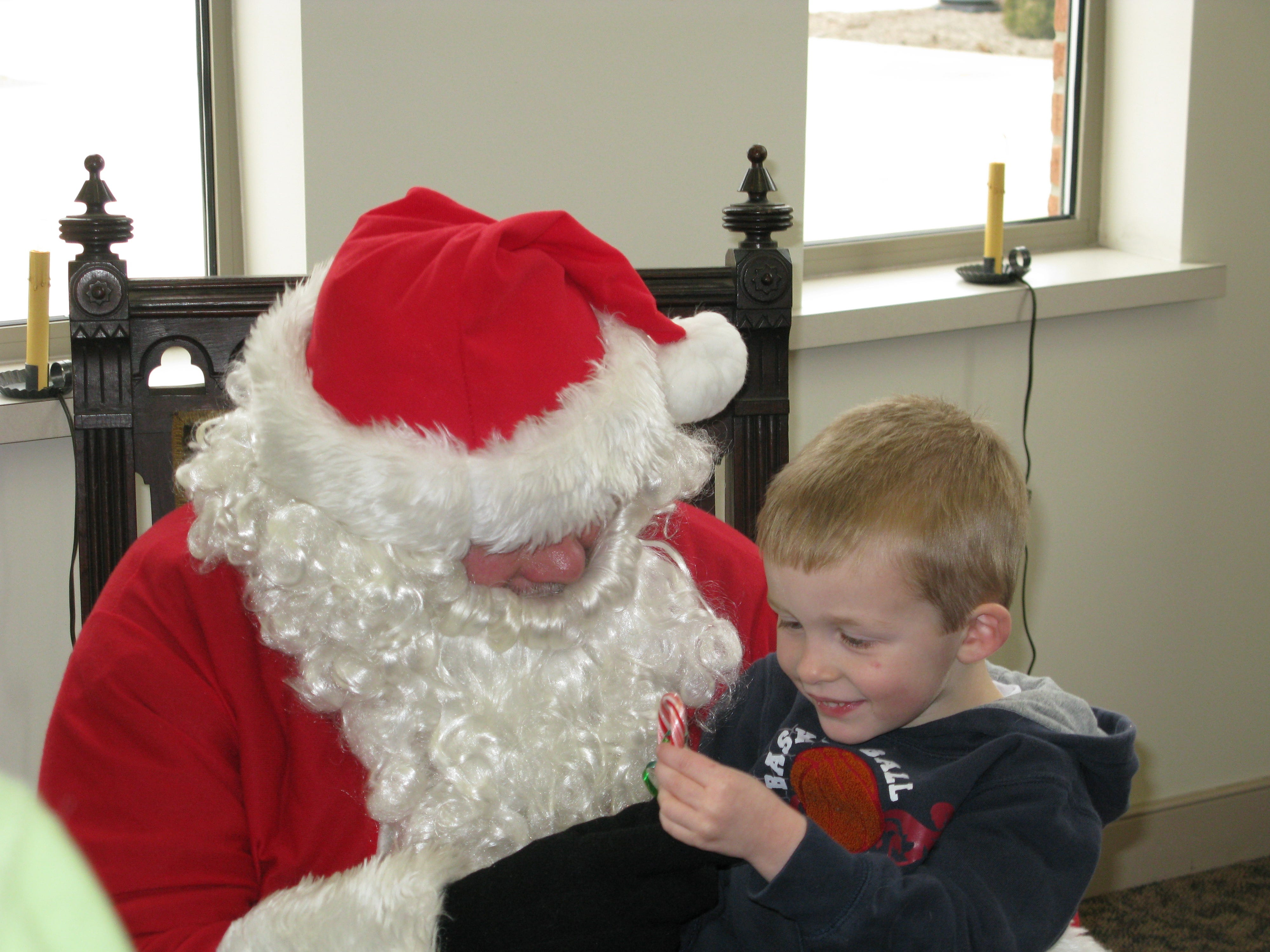 Logan Faust, 3, of Mansfield, examines his candy cane after consulting with Santa at First Citizens National Bank during Mansfield's Home for the Holidays in 2008.