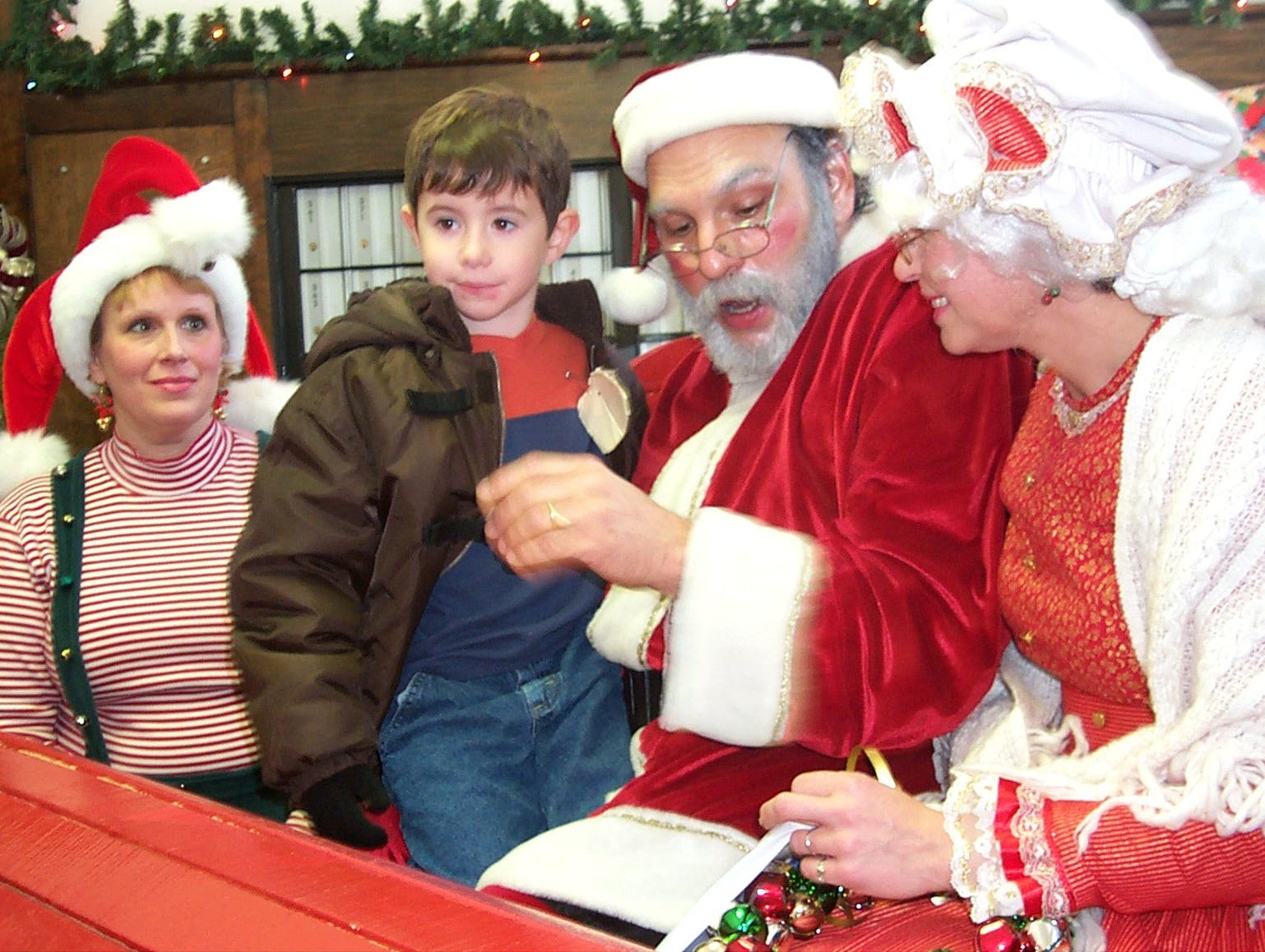 11.12.2002, 1A: Greyson Perkowski, 5, a kindergarten student at Calvin U. Smith Elementary School in Corning, talks with Santa, Mrs. Claus and helper Snowflake at the Christmas event at Painted Post Post Office.