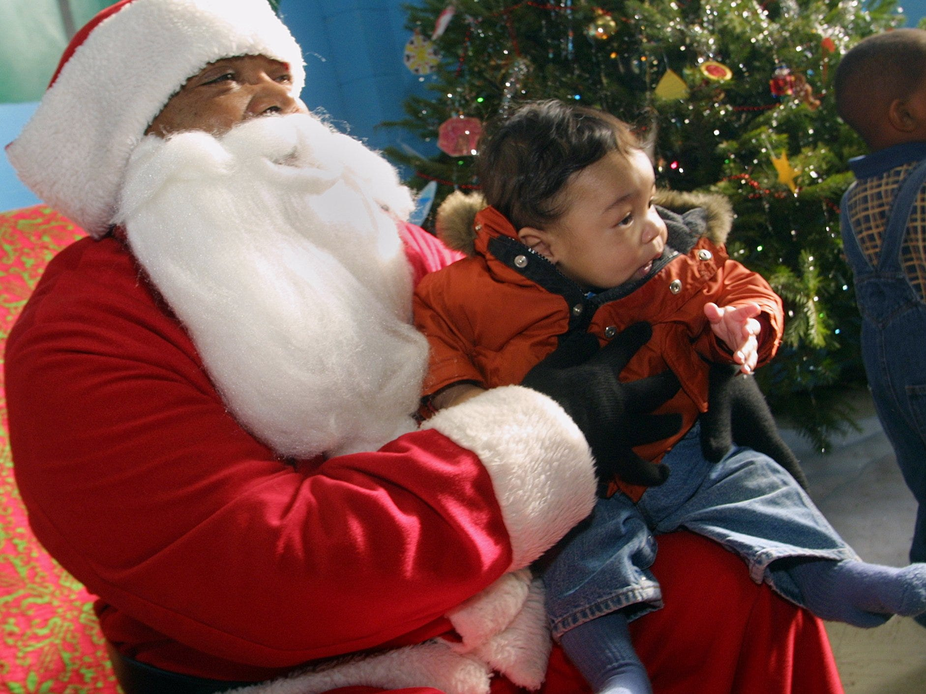 12/14/2003, 6C:    William Blye III, age 4 1/2 months, of Elmira visits Santa Claus, sometines known as Duane Johnson, during a Christmas party at the Ernie Davis Community Center on Saturday December 13, 2003.