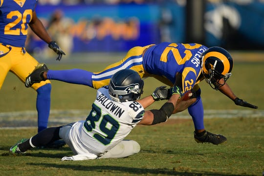 Los Angeles Rams cornerback Marcus Peters (top) is tackled by Seattle Seahawks wide receiver Doug Baldwin.